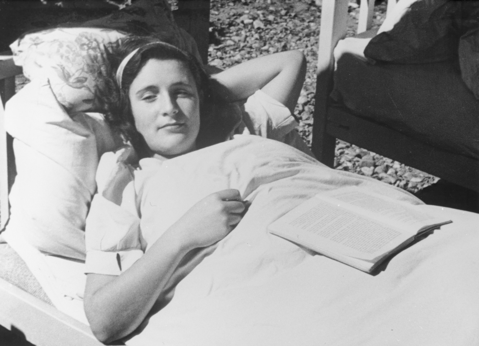 "STILL PHOTOGRAPH FROM THE NAZI PROPAGANDA FILM, ""Der Fuehrer Schenkt den Juden eine Stadt"" [The Fuehrer gives the Jews a City].  Portrait of a young Jewish woman reclining outside with a book in the Theresienstadt ghetto."
