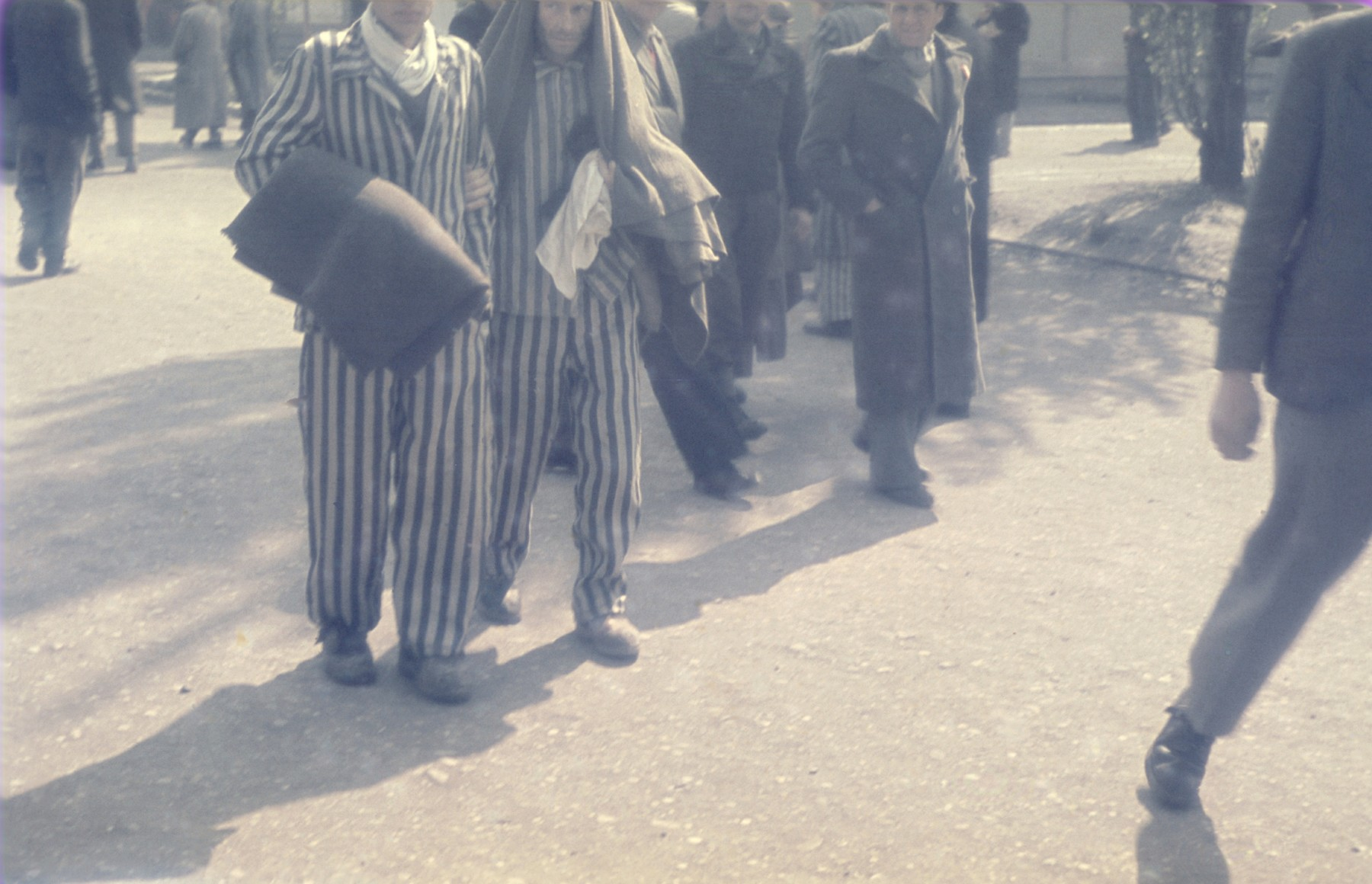 Survivors walk along the main street in the newly liberated Dachau concentration camp.