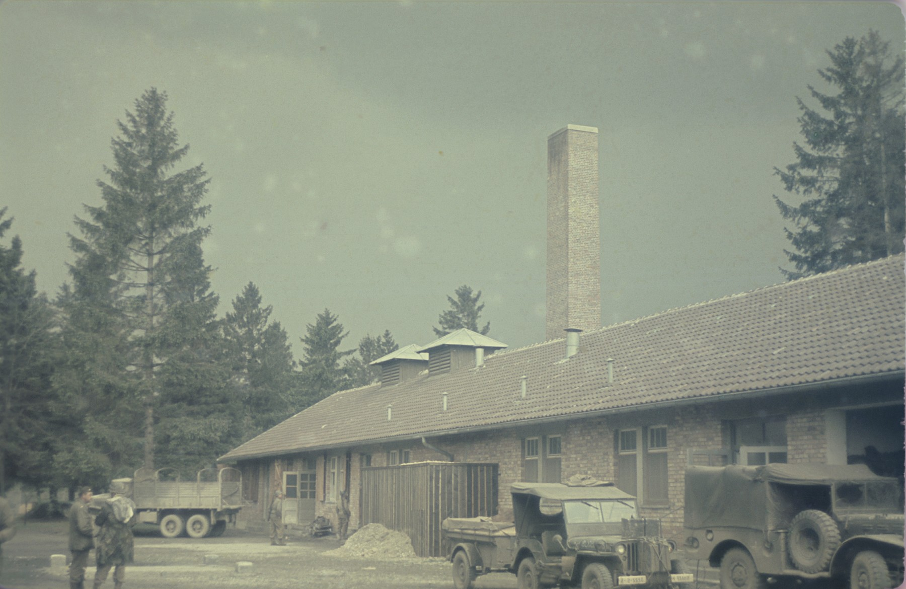 Trucks are parked in front of the crematorium in the newly liberated Dachau concentration camp.