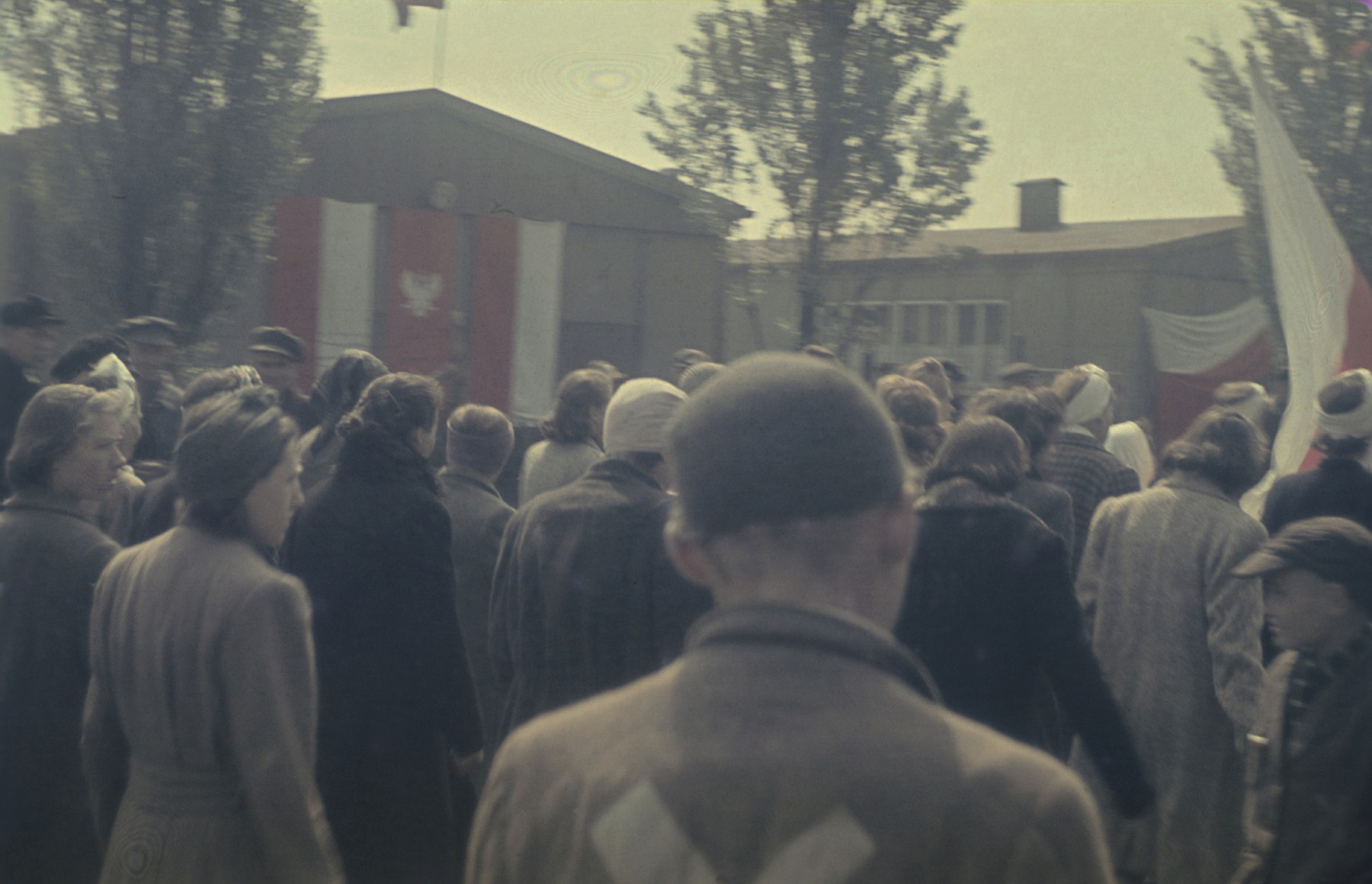 Survivors gather on the main plaza in the newly liberated Dachau concentration camp for a ceremony to salute American liberators and remember those who perished.
