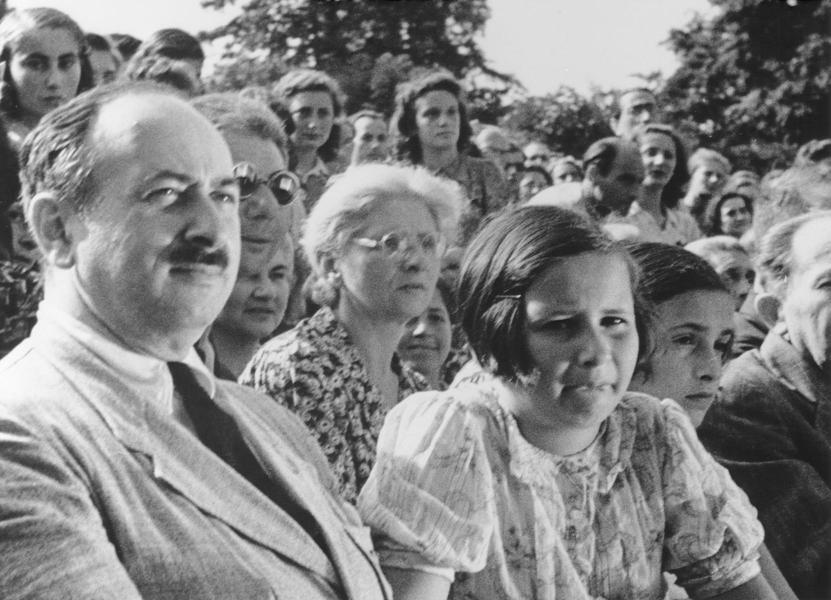 "STILL PHOTOGRAPH FROM THE NAZI PROPAGANDA FILM, ""Der Fuehrer Schenkt den Juden eine Stadt"" [The Fuehrer gives the Jews a City].  Prisoners sitting outside watch an outdoor event at the Theresienstadt concentration camp."