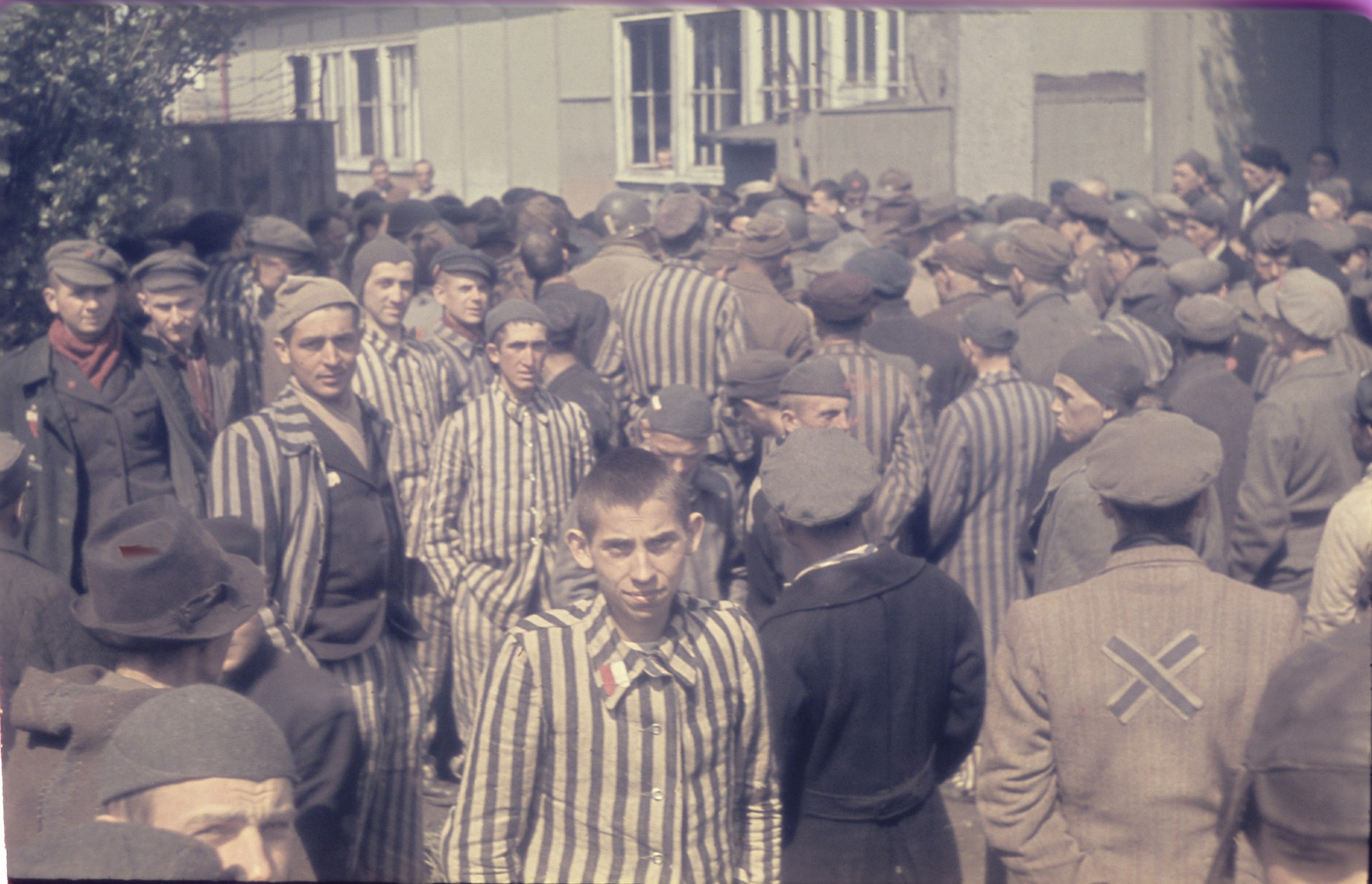 Former prisoners assemble in front of a barracks in the newly liberated Dachau concentration camp.