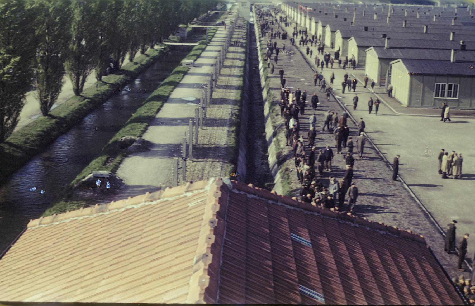 View from above of former prisoners walking along the main street of the newly liberated Dachau concentration camp parallel to the moat and the barbed wire fence.