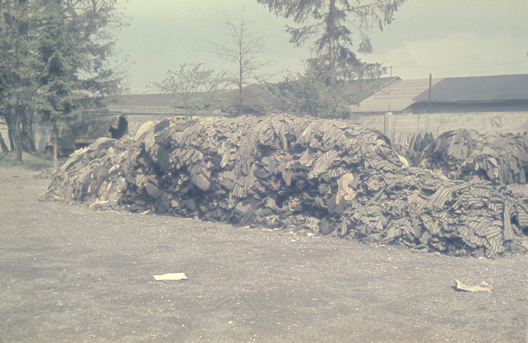 View of a huge pile of prisoner uniforms in front of a row of barracks in the newly liberated Dachau concentration camp.