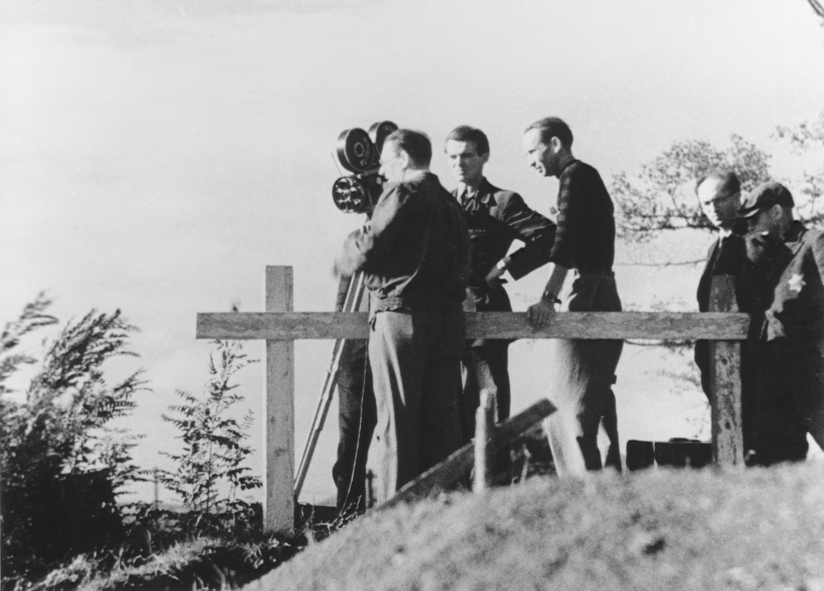 "A film crew takes motion pictures in the Theresienstadt ghetto during the filming of  the Nazi propaganda film ""Der Fuehrer Schenkt den Juden eine Stadt"" [The Fuehrer gives the Jews a City].  Ivan Fric is pictured in the middle of the film crew."