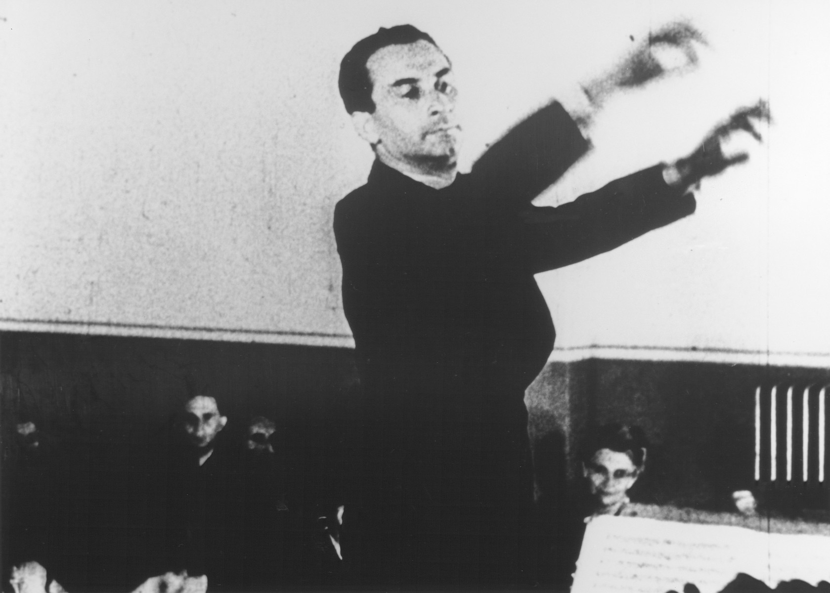 """STILL PHOTOGRAPH FROM THE NAZI PROPAGANDA FILM, """"Der Fuehrer Schenkt den Juden eine Stadt"""" [The Fuehrer gives the Jews a City].  Karel Ancerl conducts the Theresienstadt orchestra.    Karel Ancerl had been the conductor of the Prague Radio symphony.  He survived the war and became the conductor of the Toronto symphony."""