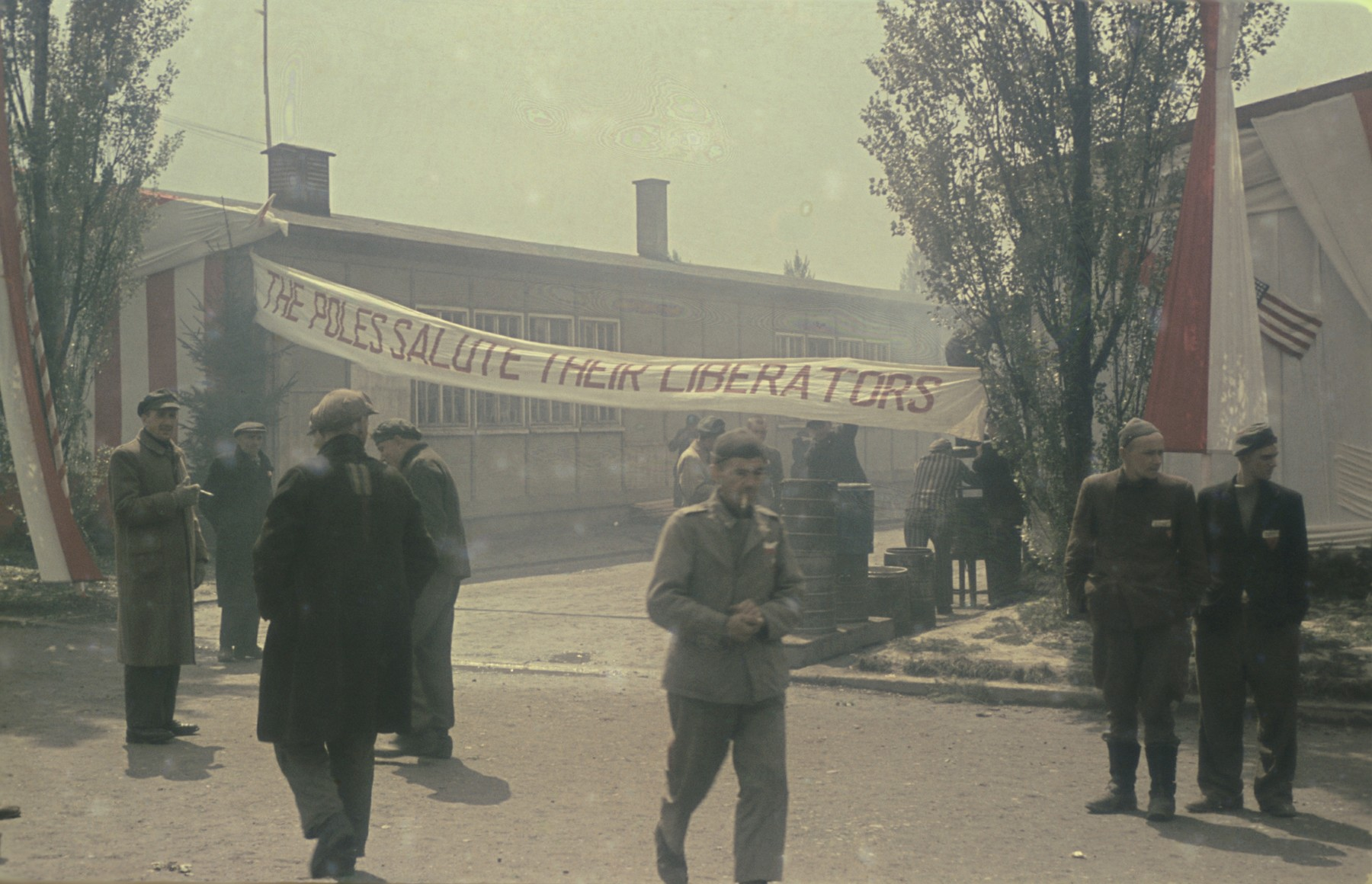 "Survivors gather on the main street of the newly liberated Dachau concentration camp beneath a banner that reads: ""The Poles salute their liberators."""