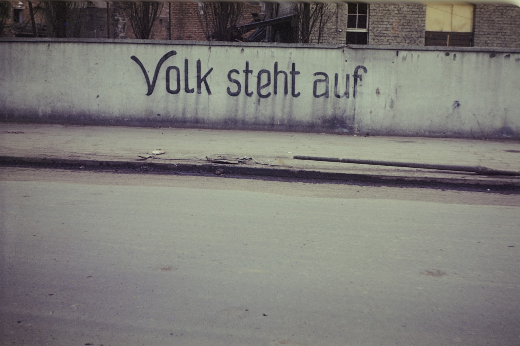 """German slogan painted on a wall in or near the newly liberated Dachau concentration camp that reads, """"People, rise up."""""""