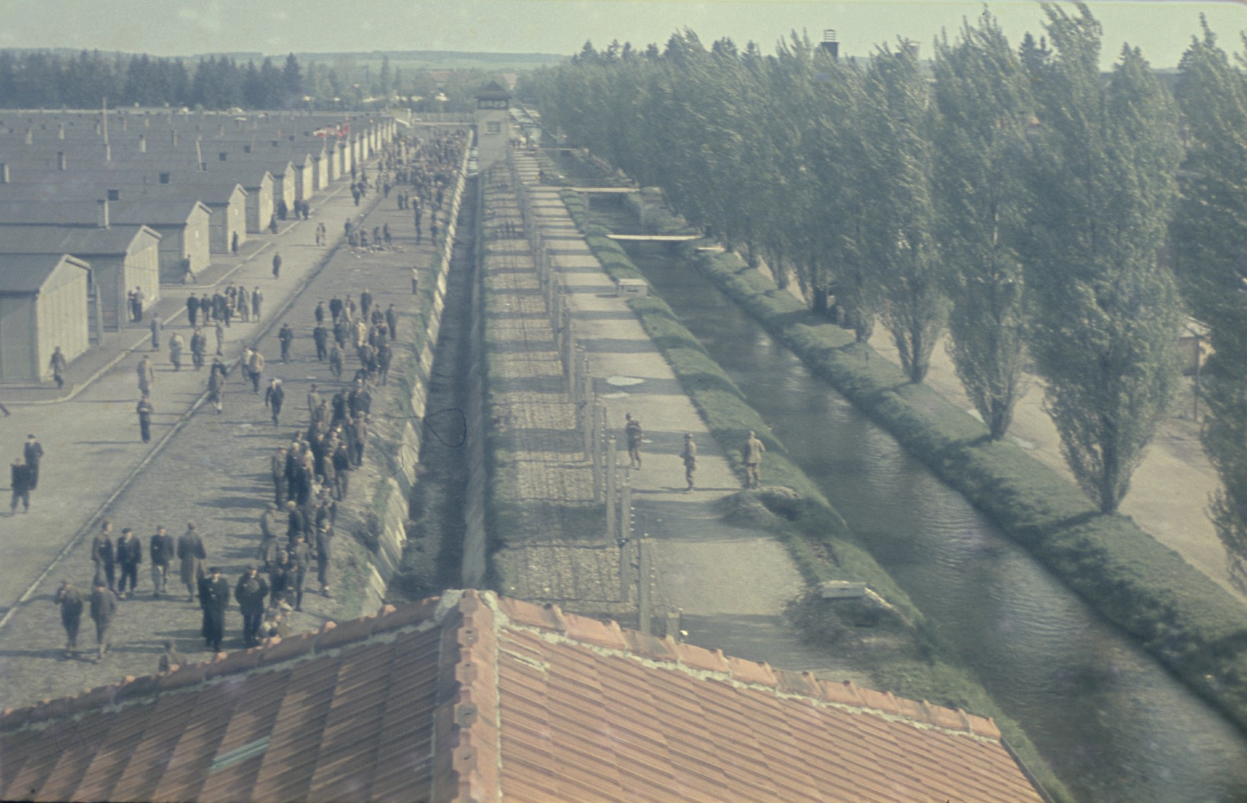 View from above of former prisoners walking along the main street of the newly liberated Dachau concentration camp parallel to the moats and barbed wire fence.