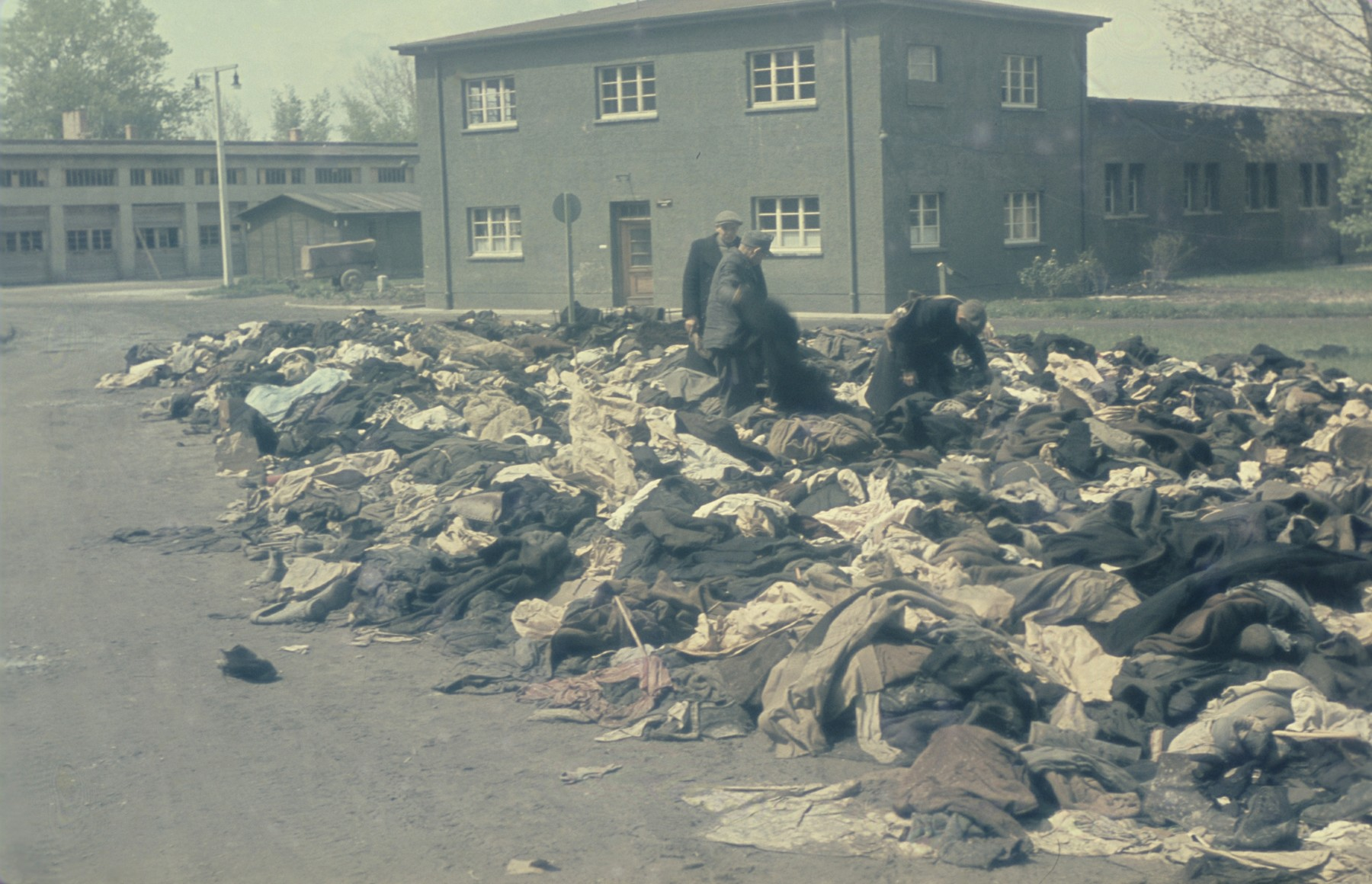 Survivors search through a huge pile of prisoner clothing in the newly liberated Dachau concentration camp.