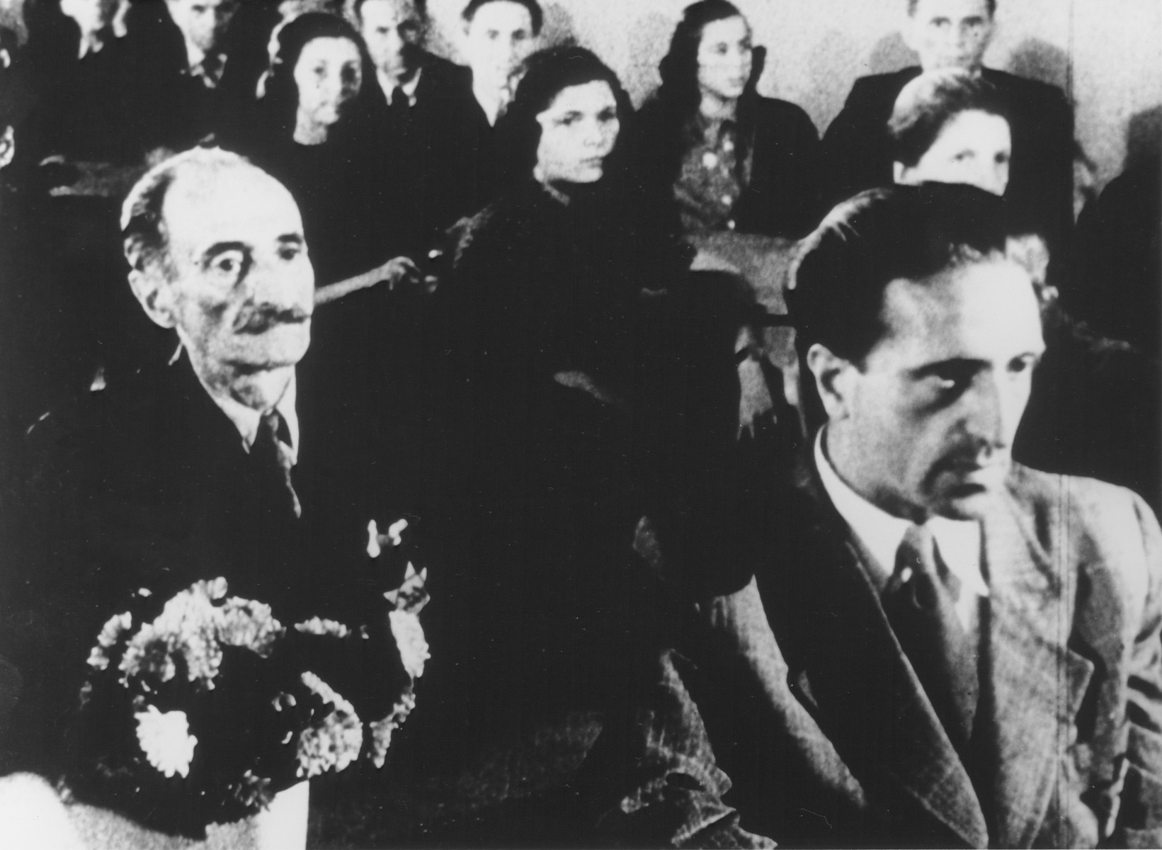 "STILL PHOTOGRAPH FROM THE NAZI PROPAGANDA FILM, ""Der Fuehrer Schenkt den Juden eine Stadt"" [The Fuehrer gives the Jews a City].  Jews watching a performance in the Theresienstadt ghetto.  The man on the right is Pavel Haas, who is actually listening to his Study for Strings performed by the Ghetto Orchestra"