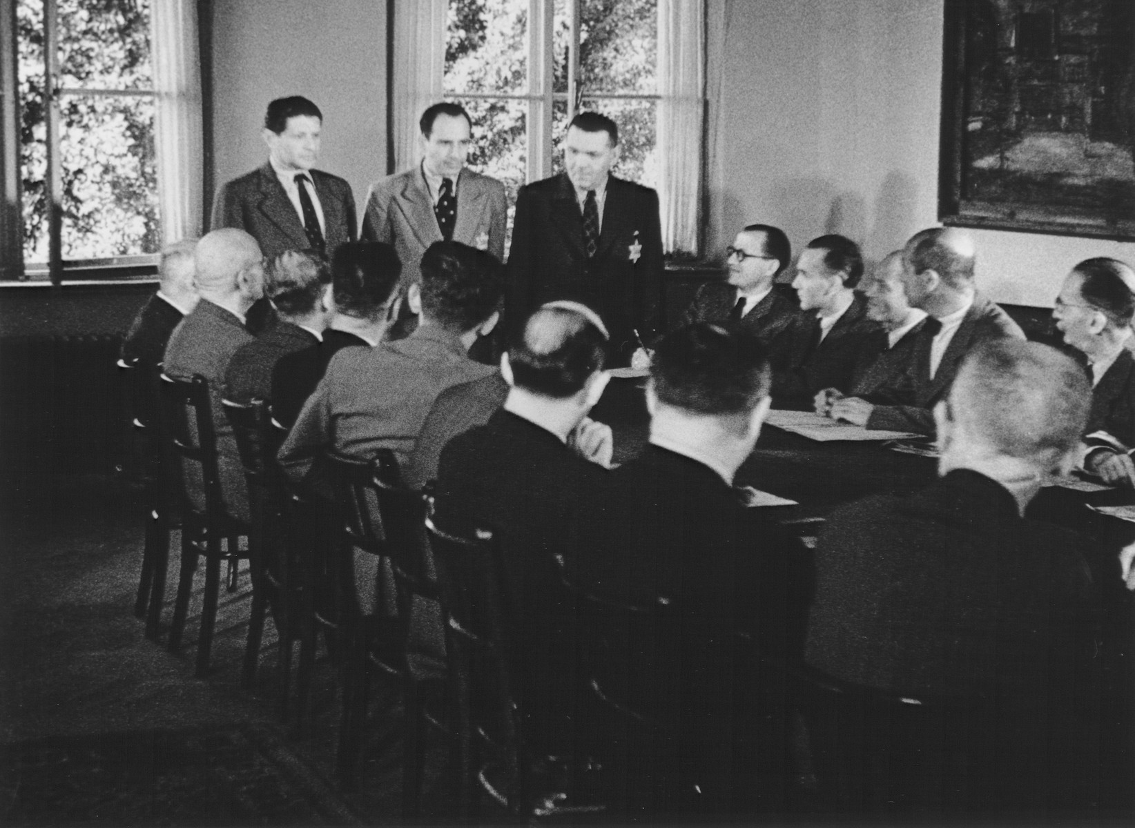 """STILL PHOTOGRAPH FROM THE NAZI PROPAGANDA FILM, """"Der Fuehrer Schenkt den Juden eine Stadt"""" [The Fuehrer gives the Jews a City].  Members of the Altestenrat (Jewish council) at a meeting in the Theresienstadt ghetto.  Pictured standing up from left to right: Otto Zucker, Paul Epstein, and Benjamin Murmelstein."""