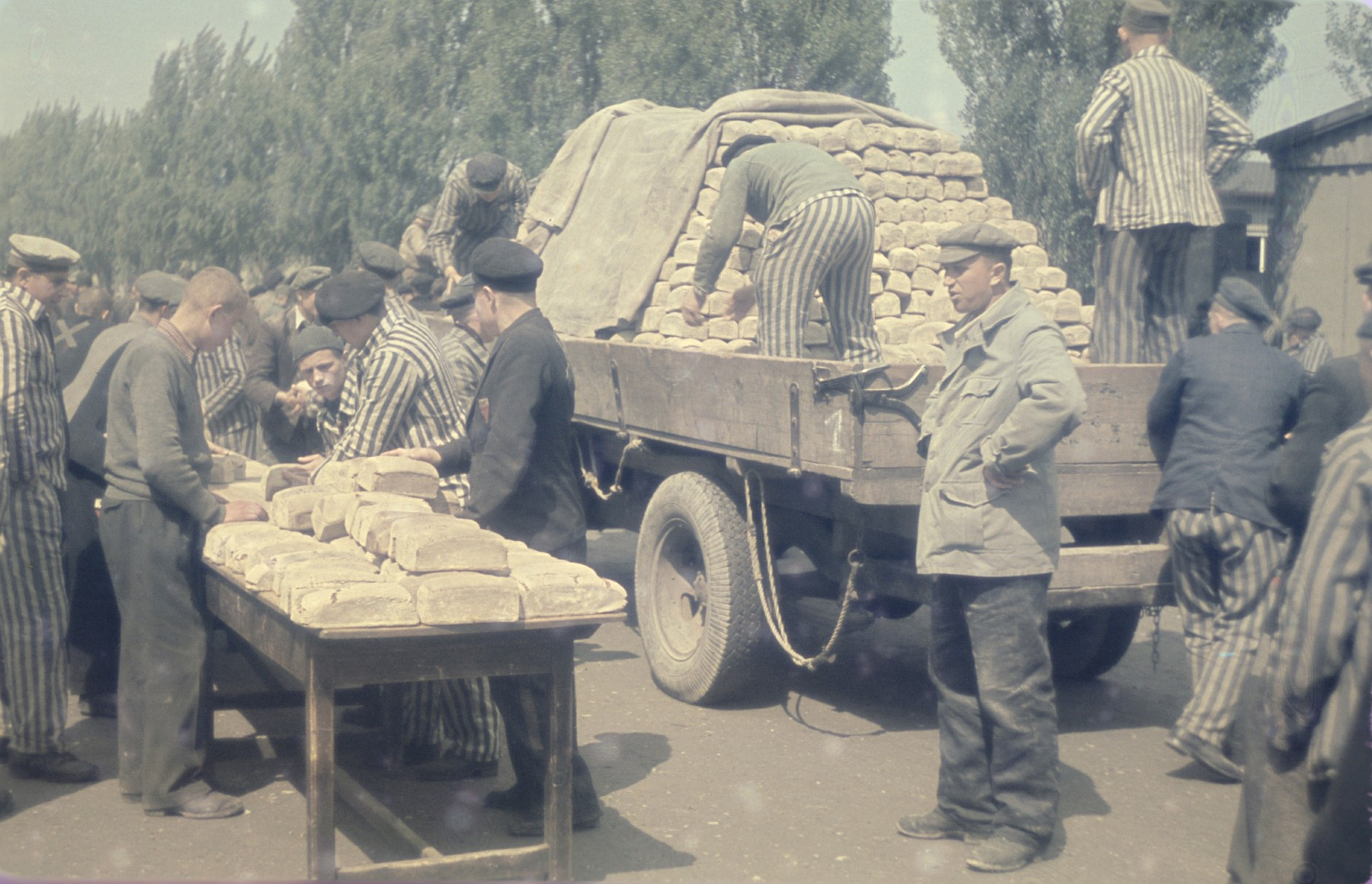 Survivors unload a supply wagon of loaves of bread in the newly liberated Dachau concentration camp.