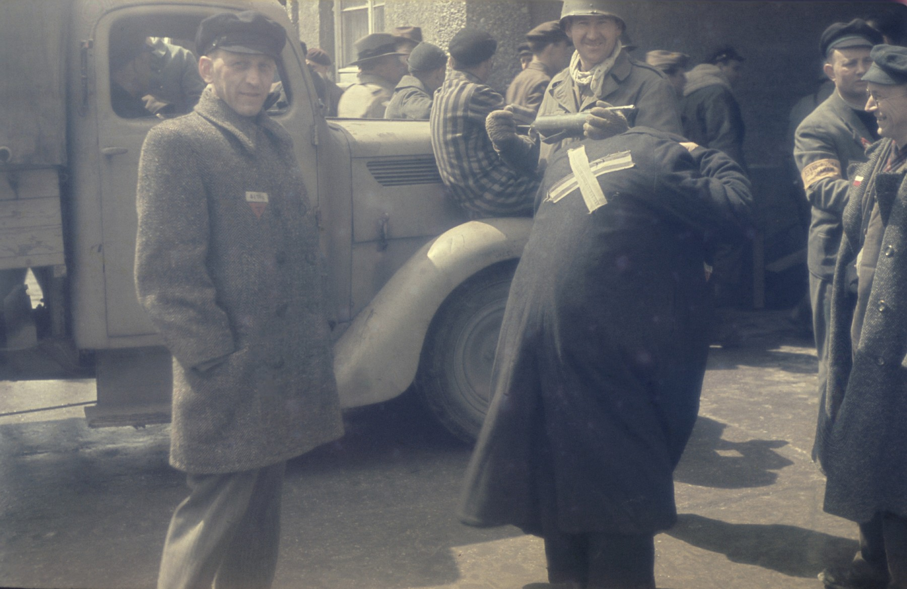 Former prisoners congregate around a truck near the entrance to the newly liberated Dachau concentration camp.