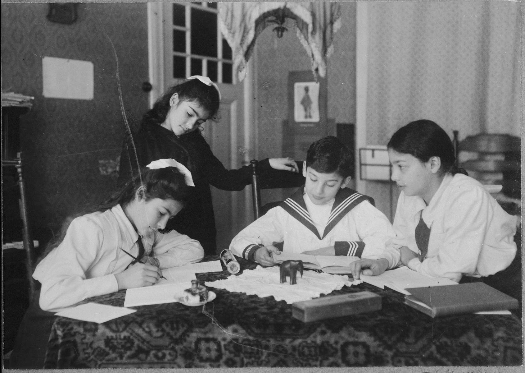Four children gather around a table in their home.    Pictured are Frieda Belinfante (standing), with her siblings Renee, Robert, and Dorothea (Dolly) (left to right).
