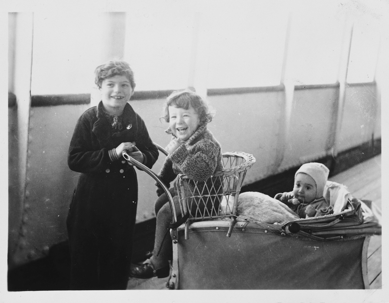Alfred and Eva Israel sit in a chair and baby carriage on the deck of the Usambara while en route to America from Germany.
