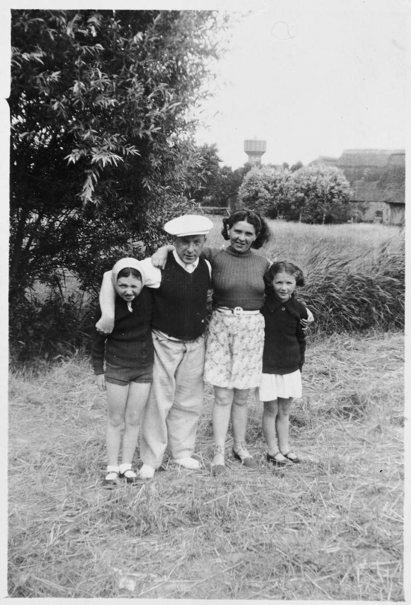 Members of the Kohn family pose outside in a field.  Pictured from left to right are Hena, Herschel, Ita Rivka and Pola Kohn.