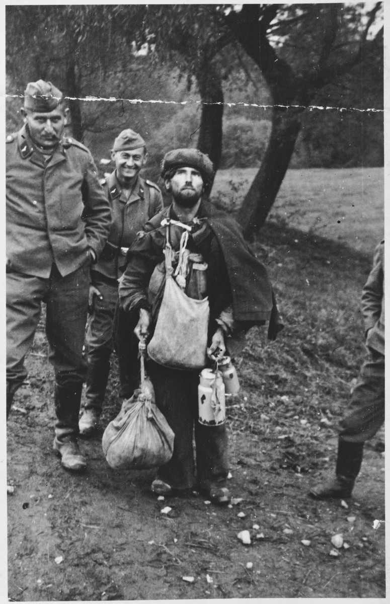 German soldiers mock a Jewish peddlar.  This photograph was taken by a German soldier and then confiscated by American serviceman Pfc. Fred Arthur Porkka after his capture.