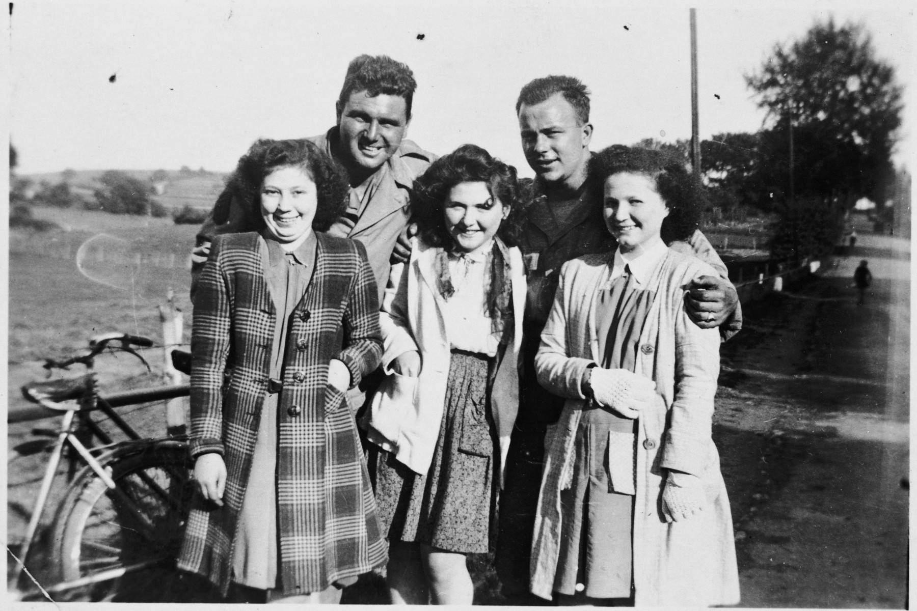 Hena Kohn and two other Jewish girls who had been in hiding pose with American soldiers after the liberation.