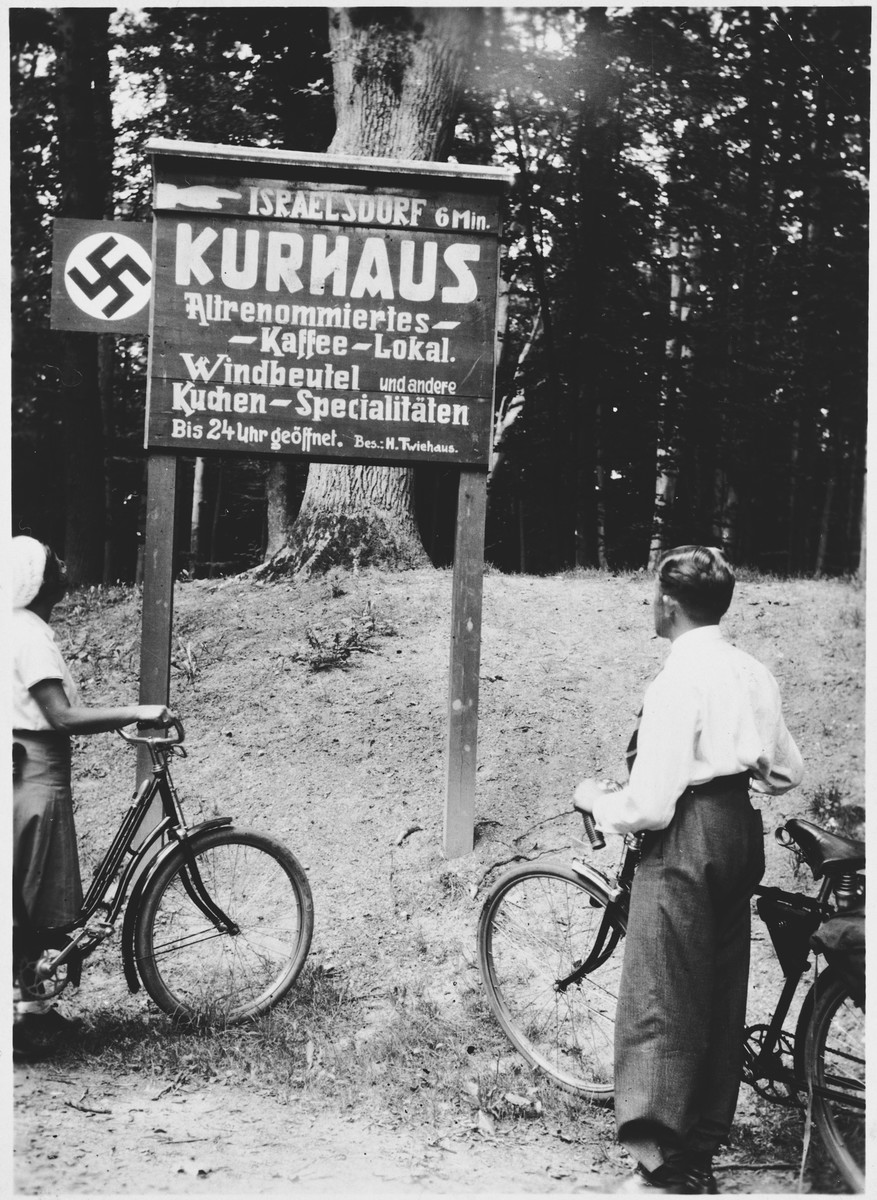 Berta Spiro and Hans Israel examine a Nazi sign declaring that Israeldorf is six kilometers away while on a bicycle trip through Germany.