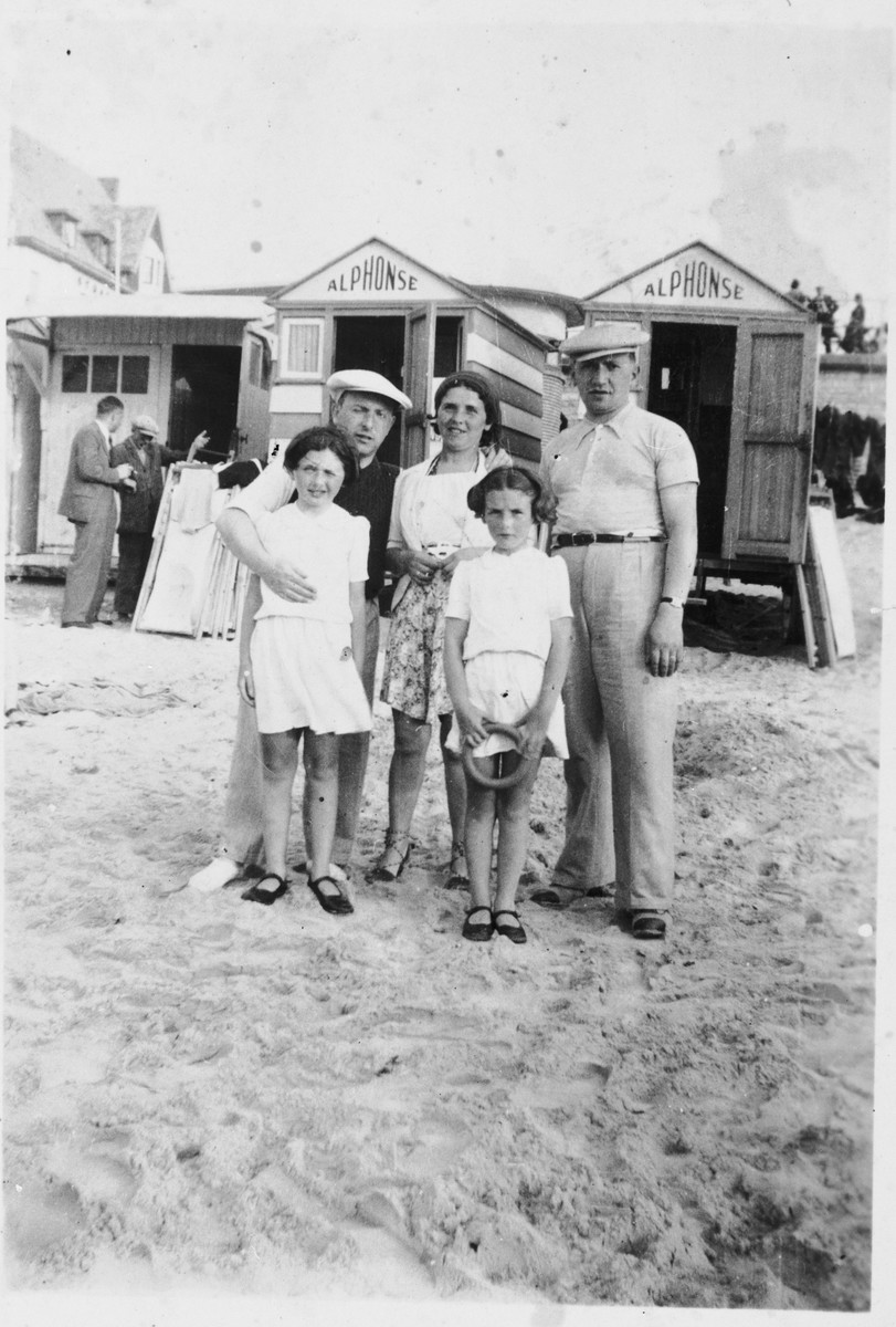 Members of the Kohn family pose outside a row of cabanas at the beach.
