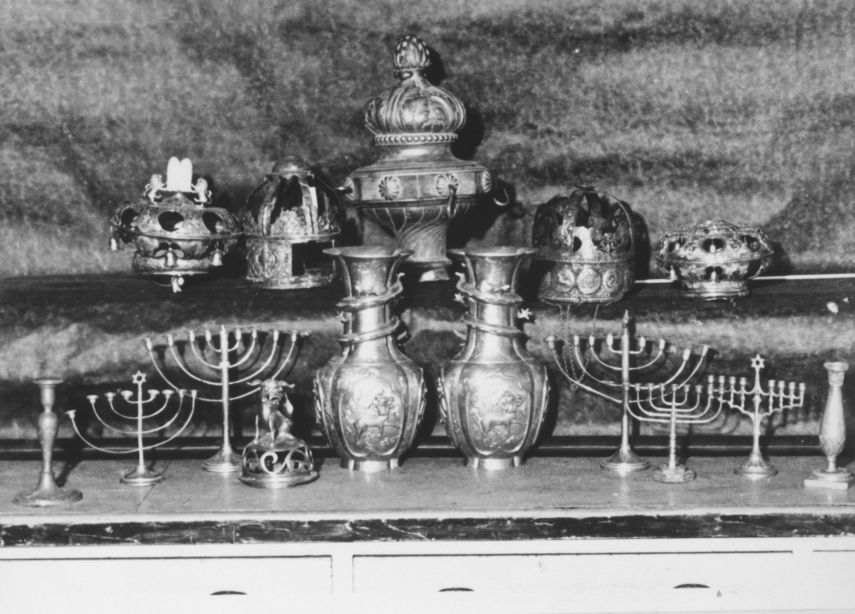 Display of silver Hanukkah menorahs, torah crowns and other ritual articles confiscated by the Nazis.