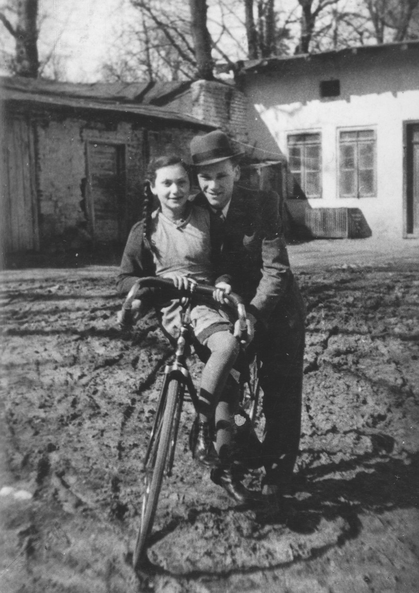 Vrumek Stapler poses with his younger sister Helcia  who is sitting on  a bicycle.
