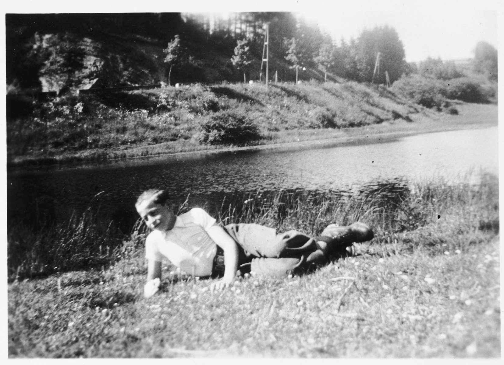 Jeannot, a young boy rescued by the priest Edouard Robert, lies down on the banks of a river.