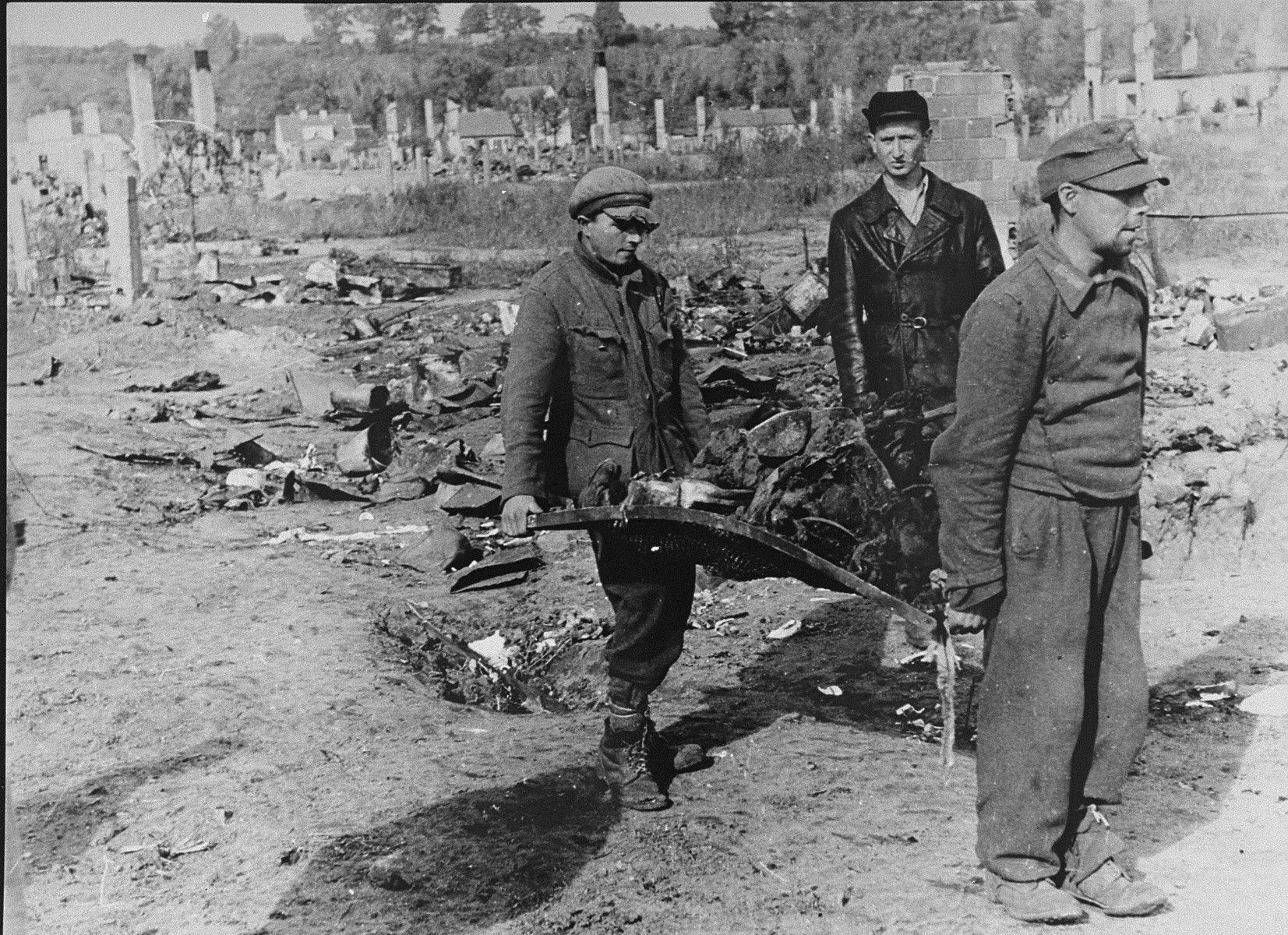 Under the supervision of a Soviet policeman, the charred remains of Jews from the Kovno ghetto are carried on a makeshift stretcher to a mass grave.  The man in the foreground appears to be a German POW.  Behind him is Moshe Volbershteyn, a member of the Zionist underground who is working for the Chevre Kaddisha, Jewish burial society.