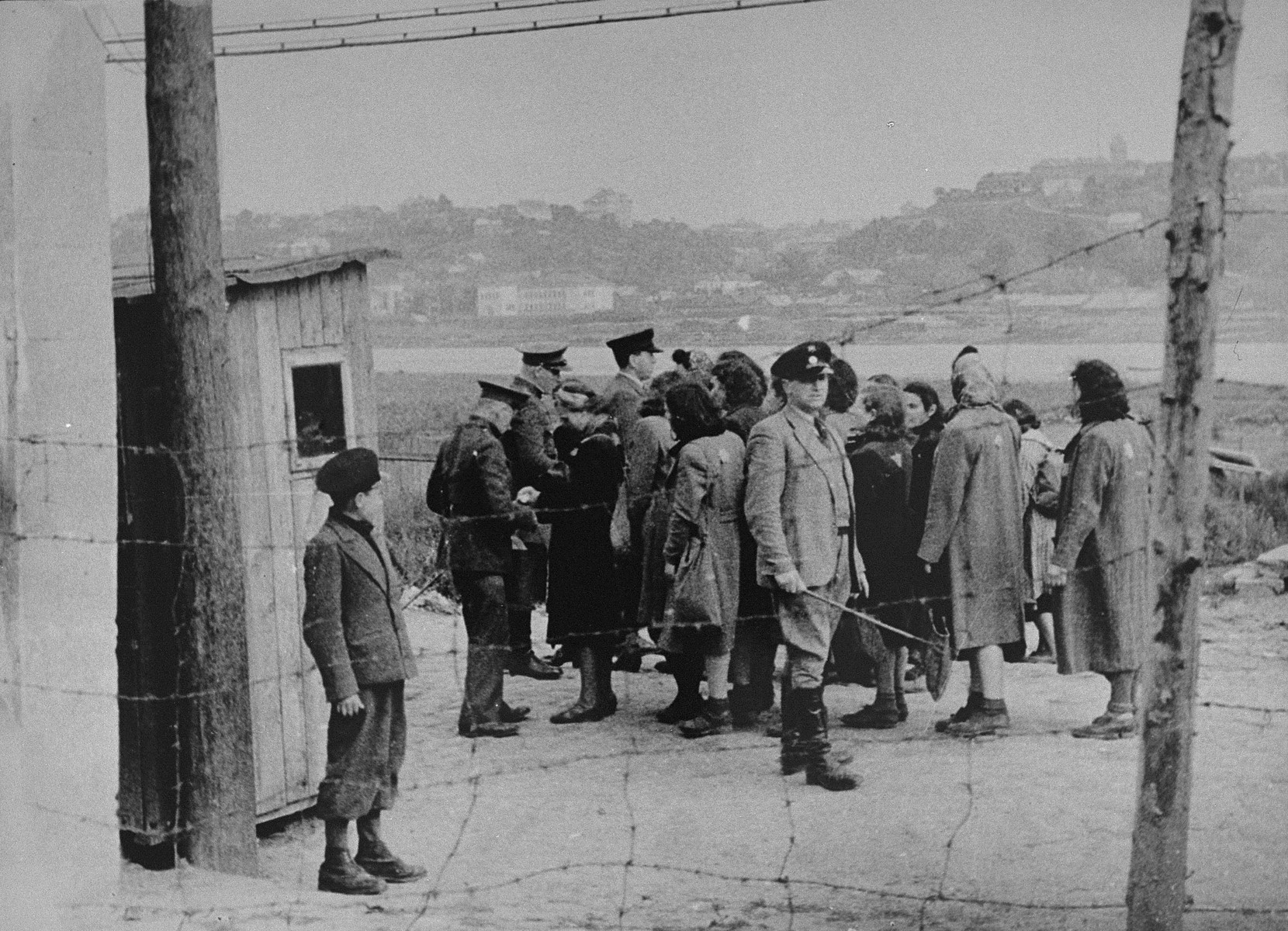 A group of Jewish women return to the ghetto after a day of forced labor on the outside. They line-up to be searched by German and Lithuanian guards.  Tanchum Aronstamm of the Jewish Police, with a baton in hand, supervises the group in the foreground.