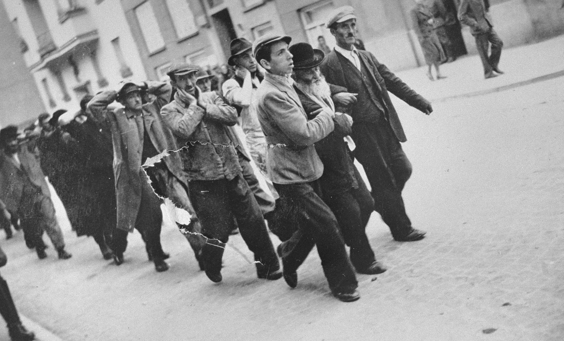 A group of Jewish men are rounded-up and marched down a street in Krakow in the early months of the war.
