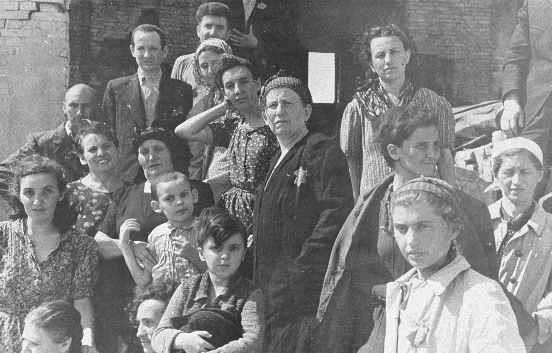 Survivors of a malina, or bunker, in the Kovno ghetto.    This bunker, under the Block C apartment complex was one of the most sophisticated in the ghetto, and one of the only to hold.  Built by the engineers Feivel Goldschmidt and Indursky, it included its own ventilation system.  Thirty four people hid in it for a total iof 38 days.    Standing on the left, third from the top is Rabbi Ephraim Oshry, behind him is Haim Leibowitz.  Seated is the dentist Bat Sheva Schmidt. Others hidden in this bunker include Basya Lipman, Mrs. Chodosh, Ida Schalansky and her children Moishe and Noachka, Yosha the butcher, Italya Garber, Berel Penkinsky. Chaim ?, Doniyel ?, Hershel ?, Mr. Dinner, Lucy Cess and Hillel Birger.  Prior to the liberation by the Soviets, approximately 6,000 Jews were deported to concentration camps in Germany.  Others went into hiding within the ghetto. The Germans used fire bombs, smoke grenades and dogs to chase people out.  Approximately 100 Jews survived in malinas or bunkers , whereas thousands either burned to death or were shot trying to escape.
