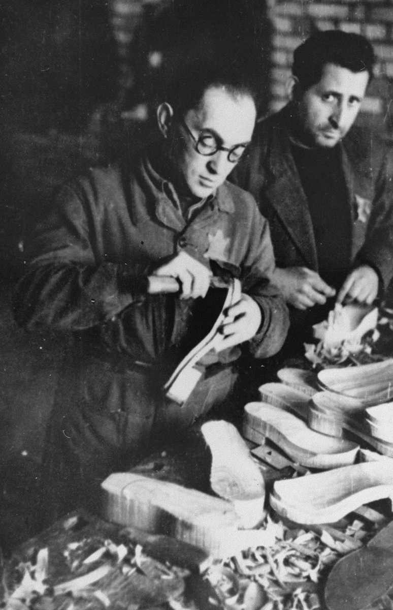 Two men fashion wooden clogs in the shoemaking workshop in the Kovno ghetto.