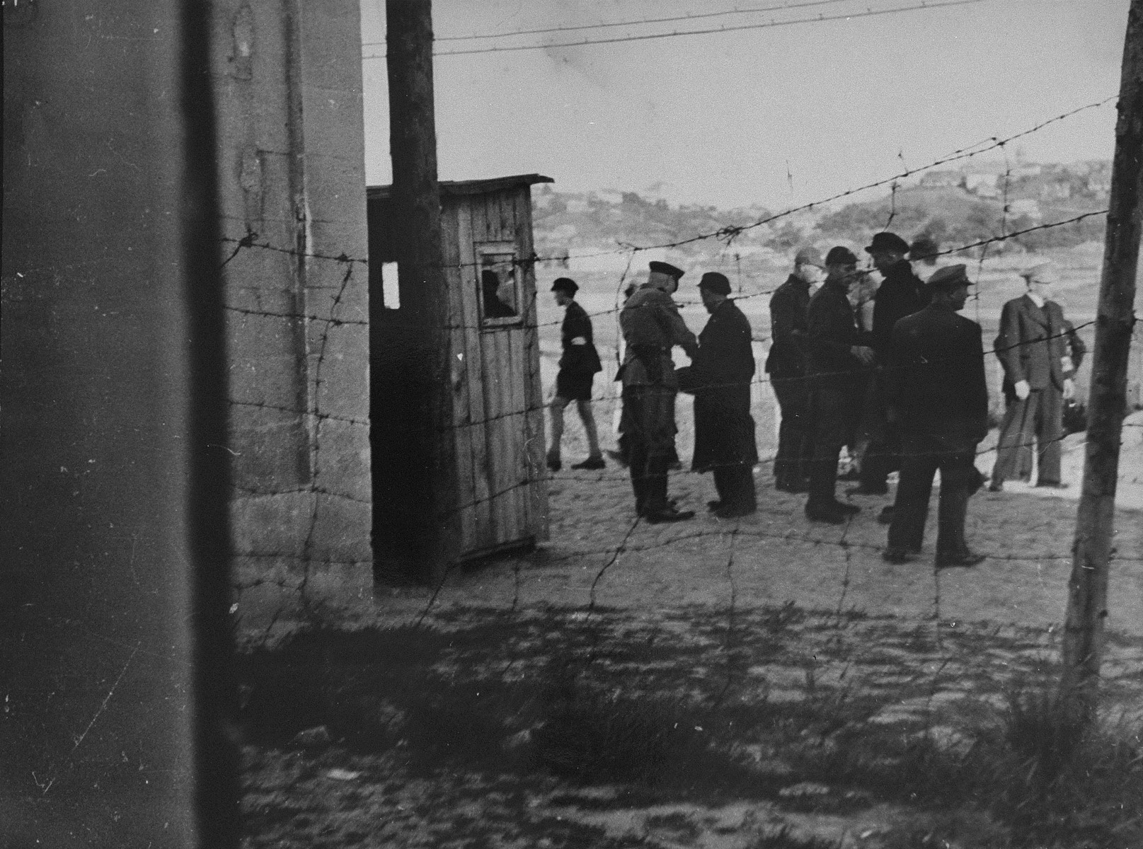 A group of Jews return to the ghetto after forced labor on the outside. German and Lithuanian guards search them as they enter. Jewish police stand among them.