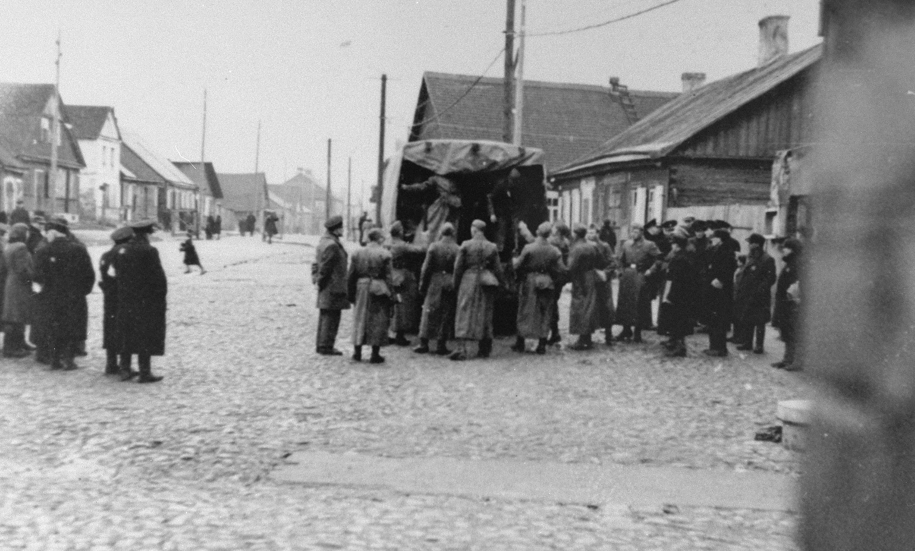 German soldiers prepare for a raid in the Kovno ghetto, as some Jewish residents look on.