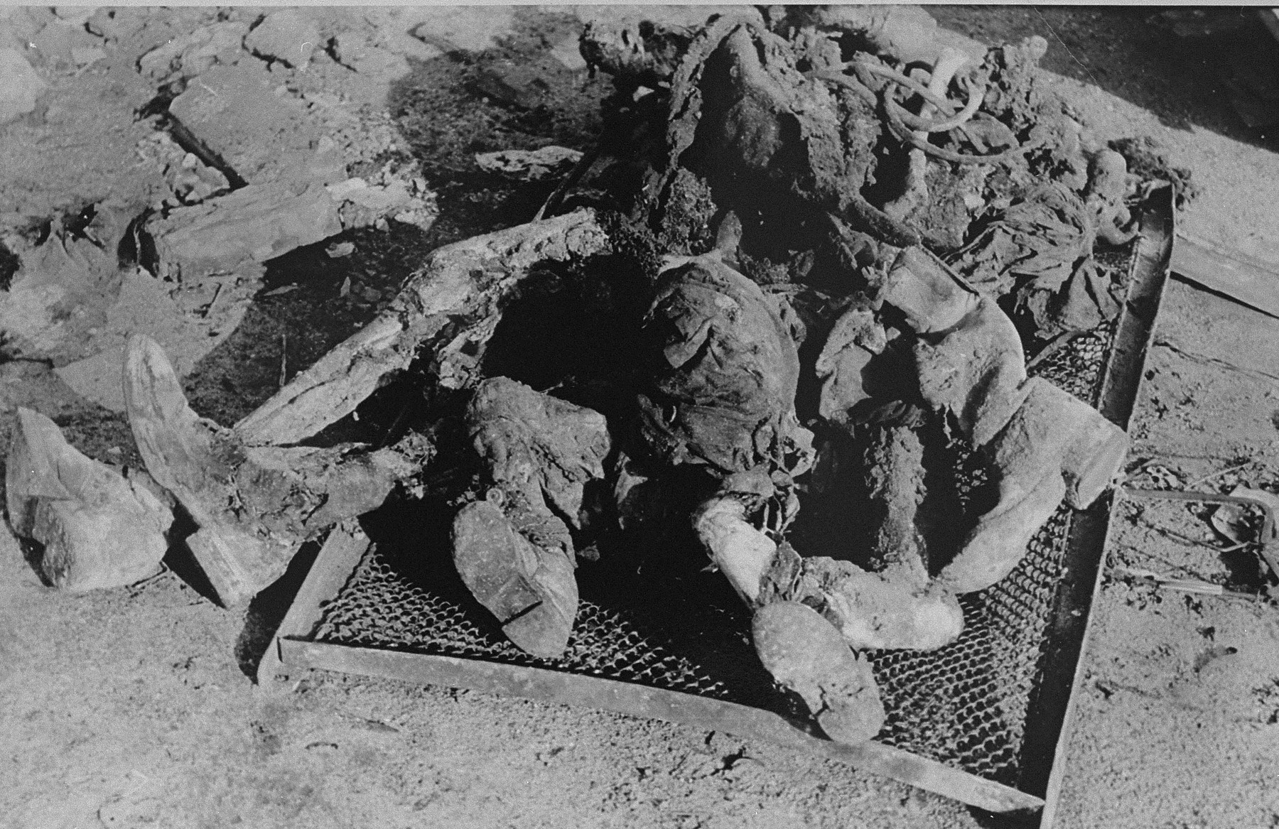 The charred corpses of Rabbi Shmukliarski, his wife and son on a makeshift stretcher after the razing of the Kovno ghetto.