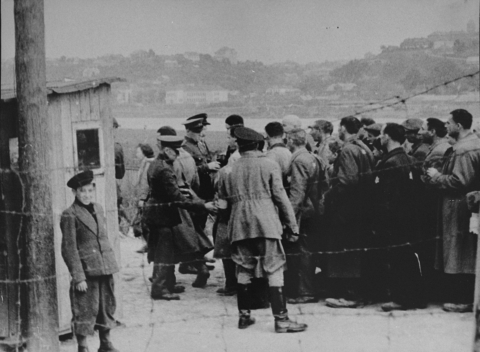A group of Jewish men return to the ghetto after forced labor on the outside.   Here, they line-up at the entrance to the ghetto to be searched by German and Lithuanian guards. A Jewish policeman stands with his back to the camera. A boy poses near the barbed-wire fence.  The Jewish men had to remove their hats in the presence of a German; the bald man in the center is Yankel Meishe Velikoludas.
