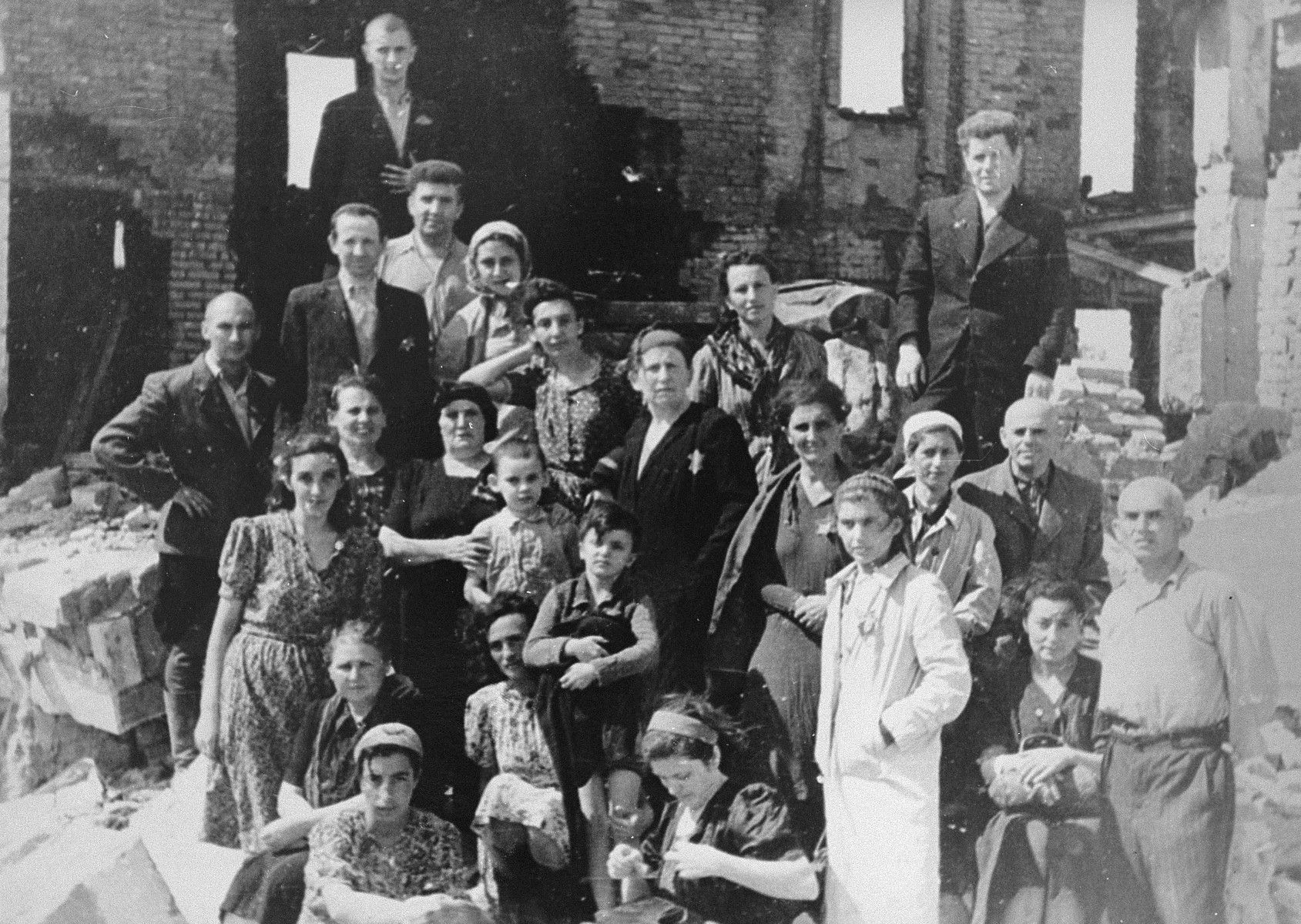 Survivors of a malina, or bunker, in the Kovno ghetto.  This bunker, under the Block C apartment complex was one of the most sophisticated in the ghetto, and one of the only to hold.  Built by the engineers Feivel Goldschmidt and Indursky, it included its own ventilation system.  Thirty four people hid in it for a total iof 38 days.    Standing on the left, third from the top is Rabbi Ephraim Oshry, behind him is Haim Leibowitz.  Seated is the dentist Bat Sheva Schmidt. Others hidden in this bunker include Basya Lipman, Mrs. Chodosh, Ida Schalansky and her children Moishe and Noachka, Yosha the butcher, Italya Garber, Berel Penkinsky. Chaim ?, Doniyel ?, Hershel ?, Mr. Dinner and Hillel Birger.  Prior to the liberation by the Soviets, approximately 6,000 Jews were deported to concentration camps in Germany.  Others went into hiding within the ghetto. The Germans used fire bombs, smoke grenades and dogs to chase people out.  Approximately 100 Jews survived in malinas or bunkers , whereas thousands either burned to death or were shot trying to escape.