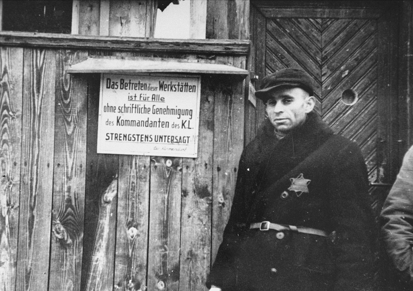 "A Jewish man standing at an entrance to a workshop in the ghetto. The sign (in German) reads, ""Entrance to this workshop is forbidden to everyone without a written permission of the camp Kommandant."""