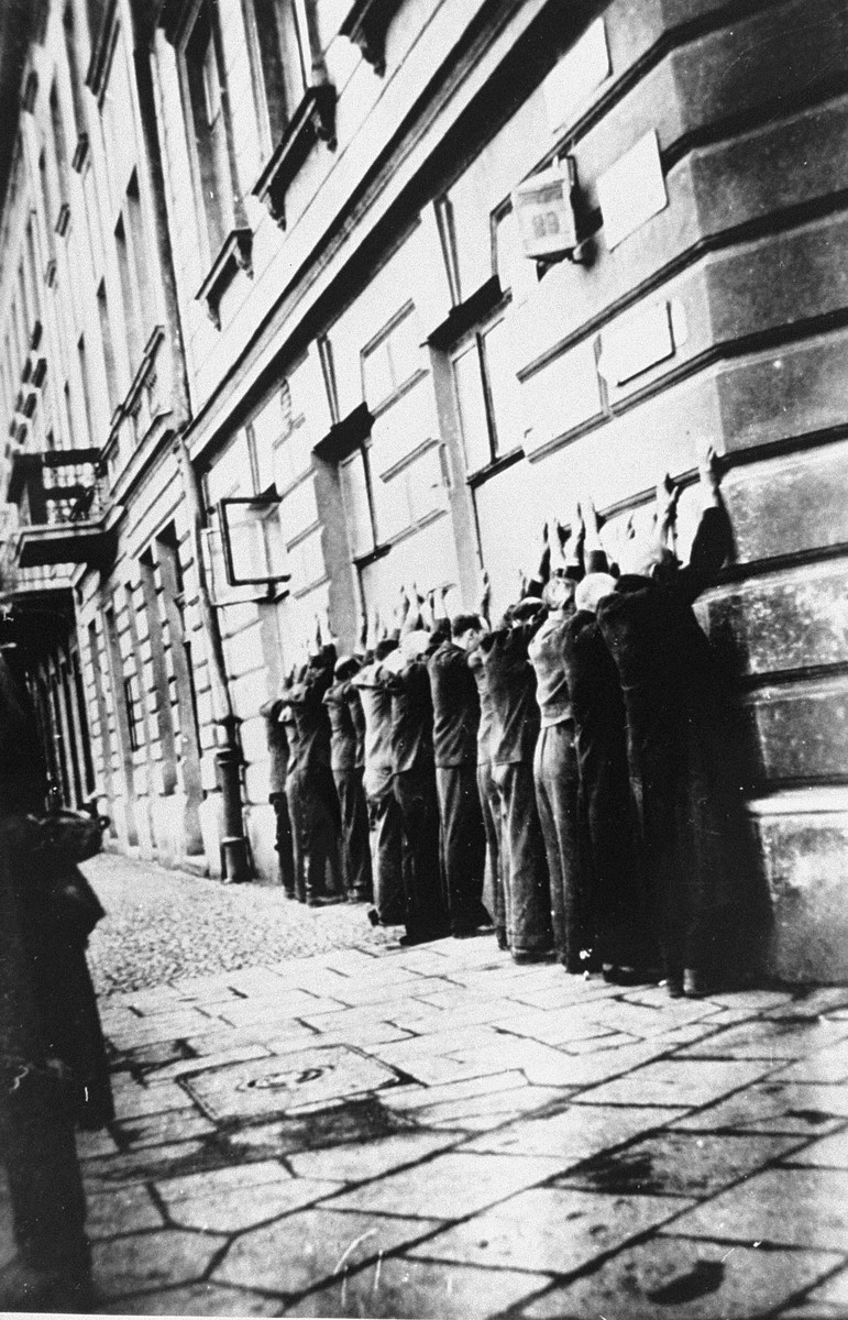 Jews arrested in the Podgorze neighborhood of Krakow are lined up along the pavement with their hands against the wall of a building.