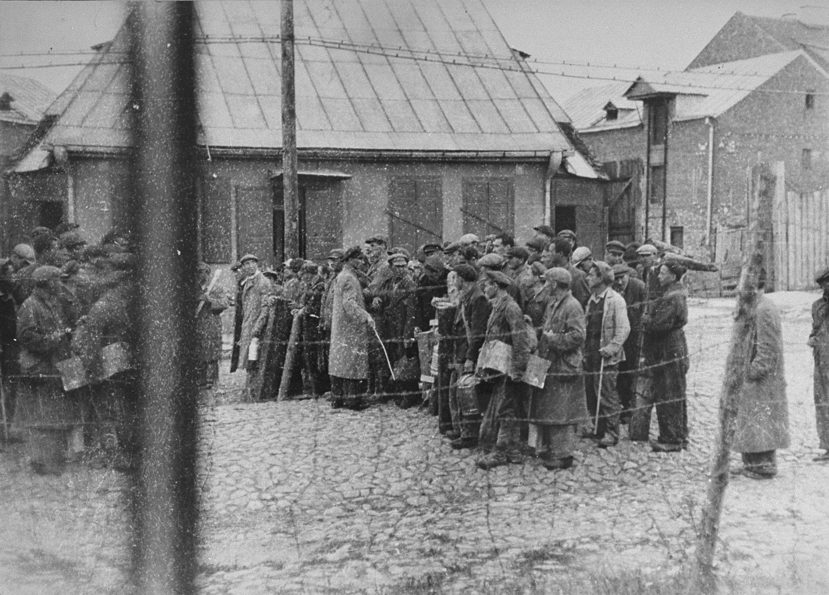 A group of Jews return to the ghetto after forced labor on the outside. They wait to be searched as they reenter the ghetto. A Jewish policeman holding a stick keeps the laborers in line.