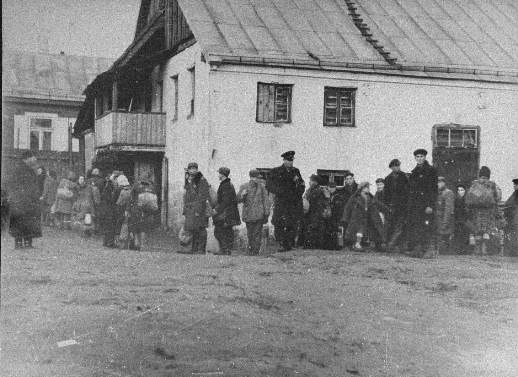 A group of Jews return to the ghetto after forced labor on the outside. Here, they line-up to be searched. Jewish police stand among them.