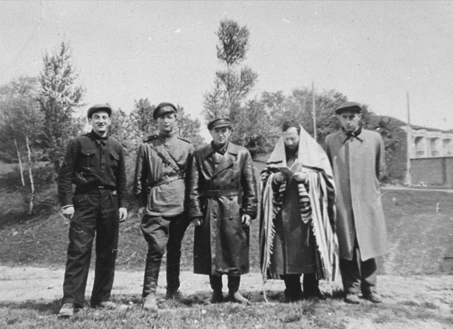Rabbi Ephraim Oshry conducts a memorial service at Fort IX ten months after the liberation.  With him are four participants in the Christmas 1943 escape from the fortress.   Pictured from left to right are: Pinia Krakinovski, Israel Gitlin, Berl Gempel, Rabbi Ephraim Oshry, and Wladyslaw Blum (?).