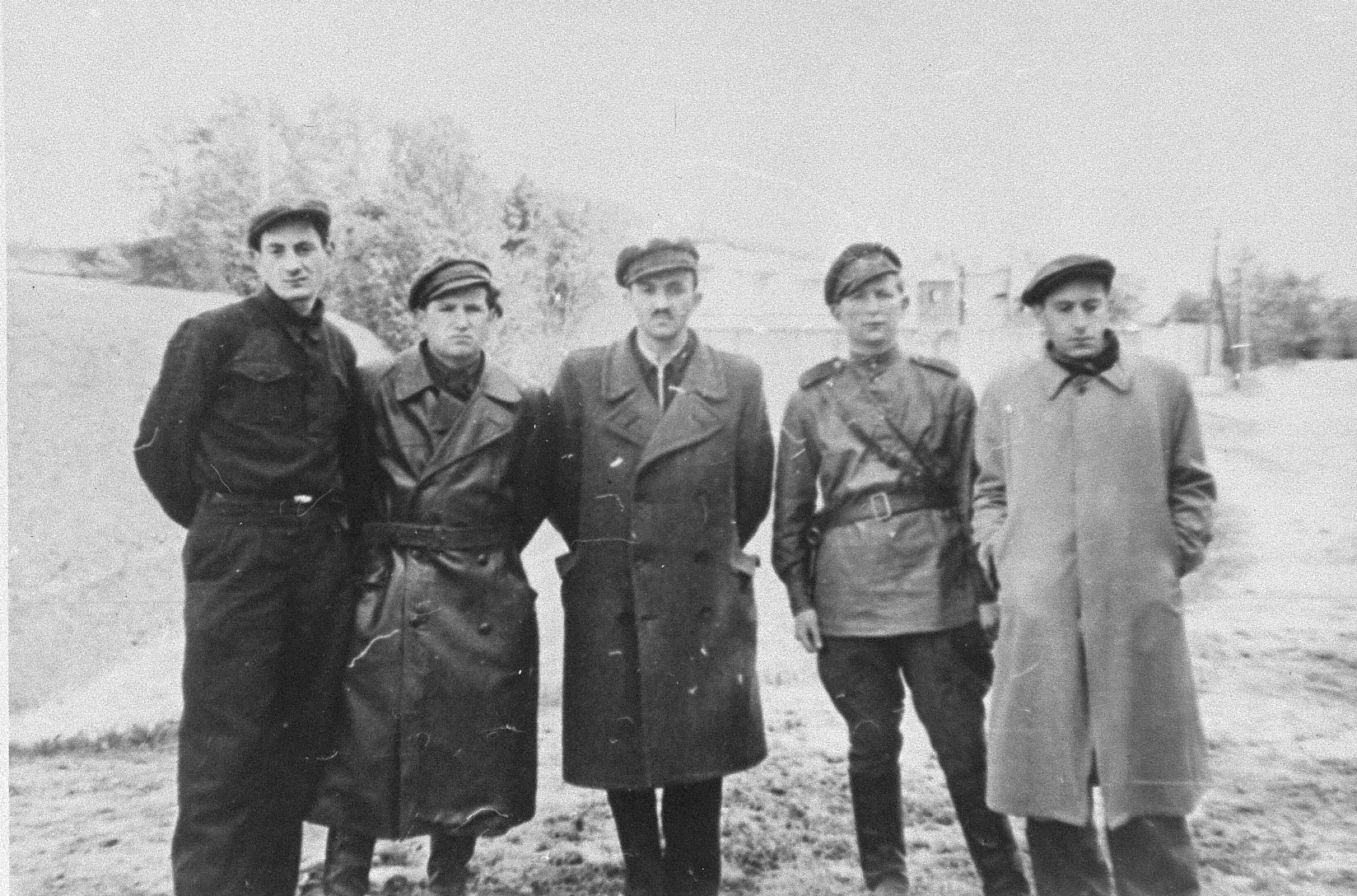 Group portrait of Jewish resistance fighters and participants in the Christmas 1943 escape from Fort IX in front of the fortress ten months after the liberation.  Pictured from left to right are: Pinia Krakinovski, Berl Gempel, Meir Yellin, Israel Gitlin and Wladyslaw Blum(?).