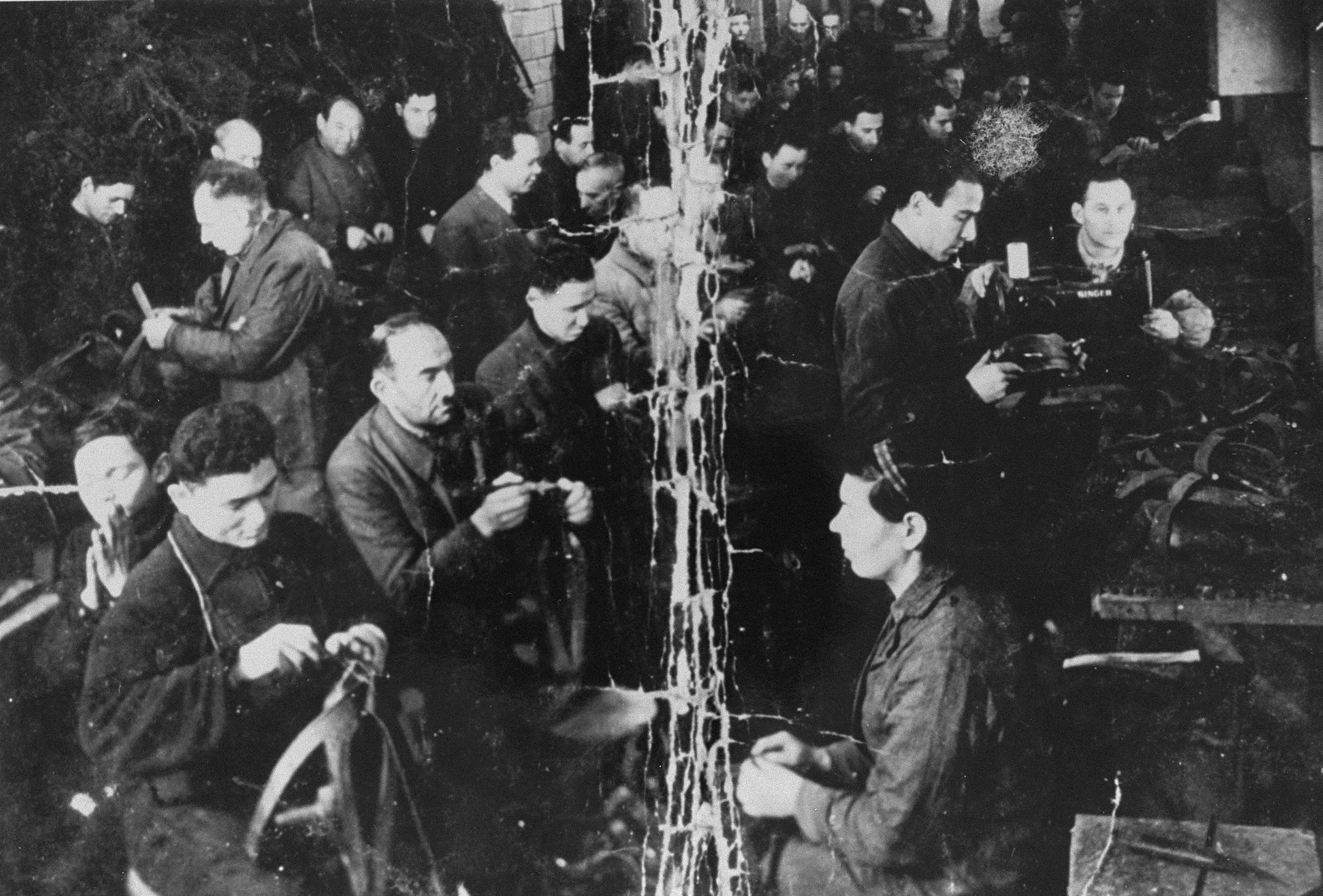 View of Jews at work in the saddle making workshop in the Kovno ghetto.    Pictured in the center to the left of the crease are Spitulnik and Baruch Grodnik. This photo was kept folded in the pocket of partisan Baruch Gofer while he was living in the forests.