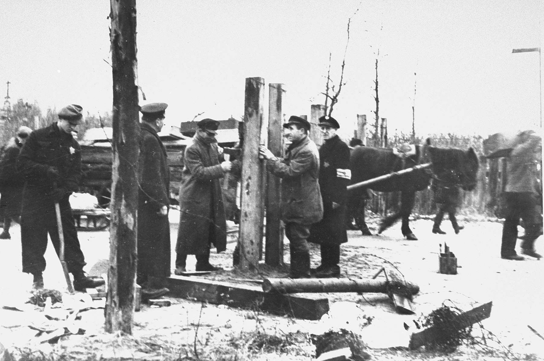 """Jews repairing or moving the ghetto fence after a reduction of the ghetto boundaries.  Pictured at the left is Abe Malnik.  Second from the right is Yankel Kaplan.  On July 24, 1941, three weeks before all Jews had to move into the ghetto, the Kovno city government ordered that the Jews erect a fence around the ghetto.  A new order stipulated that work was to begin on July 30.  Fifty men were to report to work at 8:00 in the morning for the purpose of erecting the fence.  Posts were placed one meter apart and barbed wire was strung every twenty centimeters.  Signs were posted warning that the area  within three meters of the fence was declared a """"death zone""""; anyone caught in that zone would be summarily shot.  Many Jews were shot for approaching the fence.  However, when guards were not looking, Jews and Lithuanians traded through the fence, and some Jews, using wire cutters, managed to cut the fence and escape from the ghetto.  The ghetto fire department was responsible for mainaining and repairing the fence."""