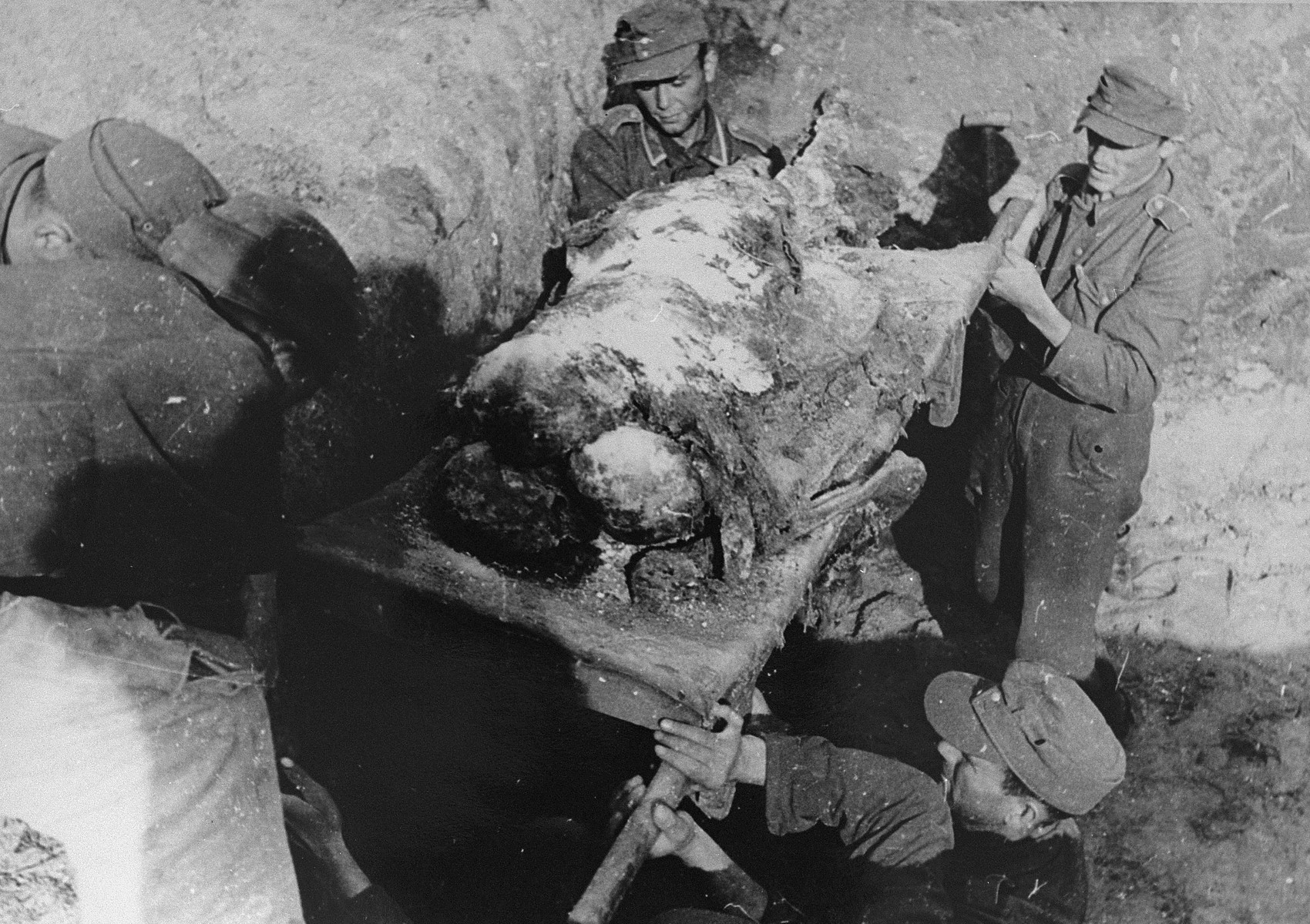 Under the supervision of Soviet officers, German POWs carry the charred remains of Jews from the Kovno ghetto on a makeshift stretcher and lower them into a mass grave.