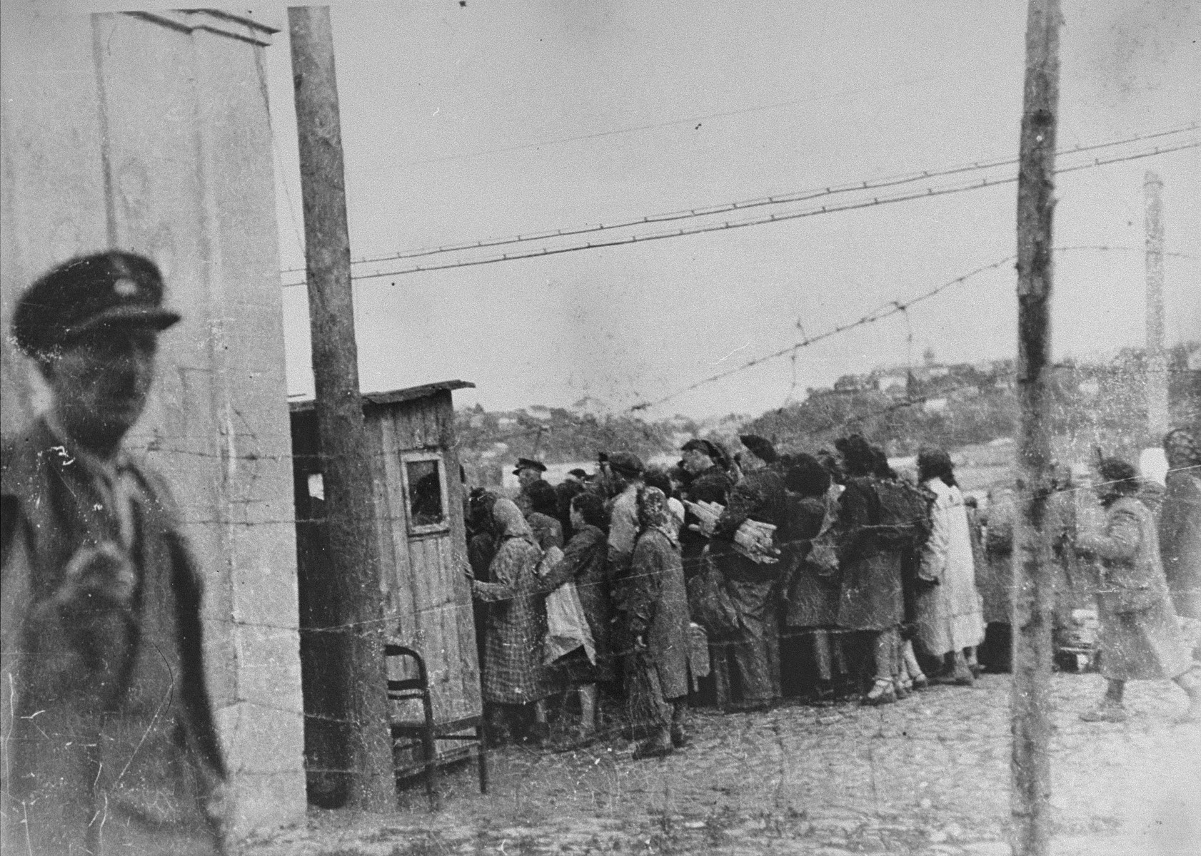 A group of Jews return to the ghetto after a day of forced labor on the outside. They line-up to be searched by German and Lithuanian guards.