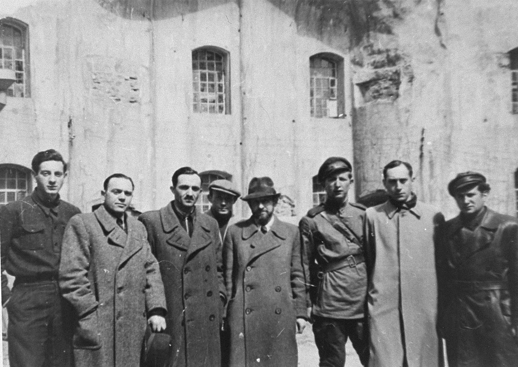 Group portrait of Jewish resistance fighters and participants in the Christmas 1943 escape from Fort IX in front of the fortress ten months after the liberation.  Pictured from left to right are: Pinia Krakinovski, Dr. Bliasberg, Meir Yellin, Zvi Kadushin, Rabbi Ephraim Oshry, Israel Gitlin, Wladyslaw Blum(?) and Berl Gempel.