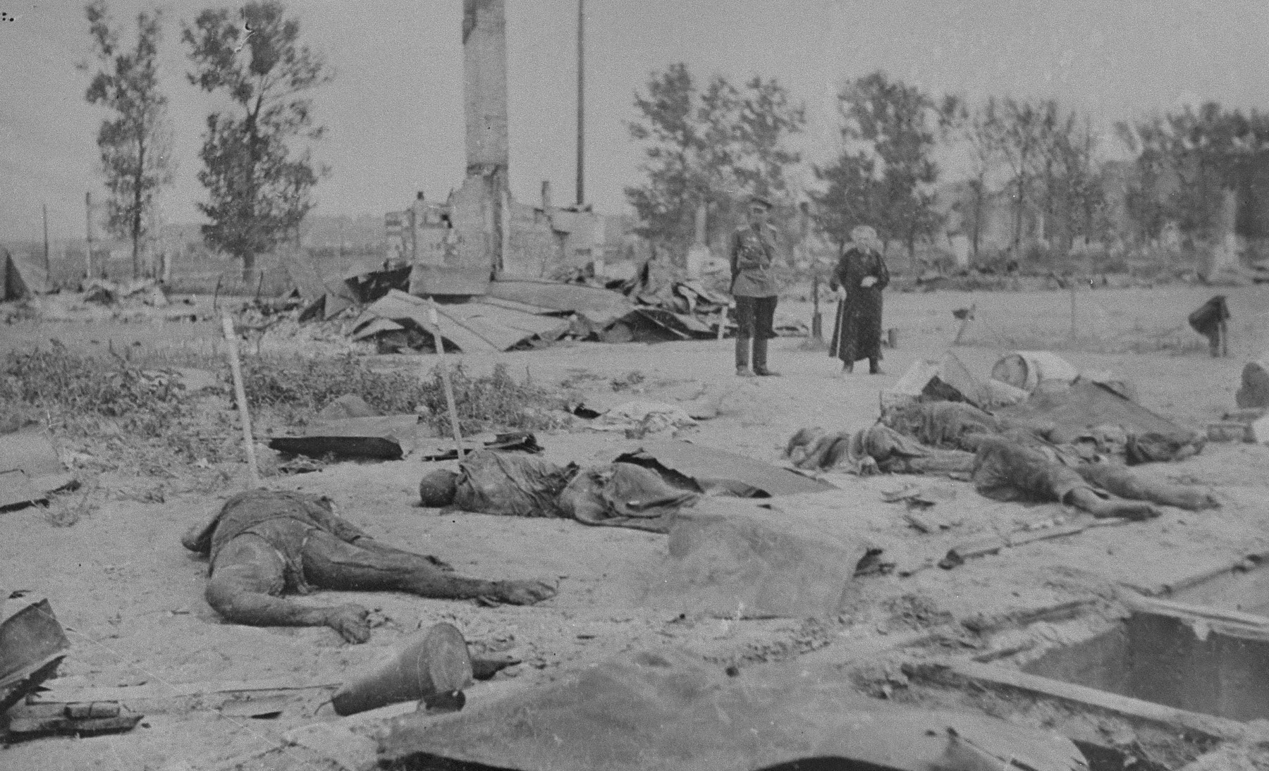 A Russian officer and an elderly woman view the devastation that resulted from the razing of the Kovno ghetto.  Charred human remains are strewn among the rubble.